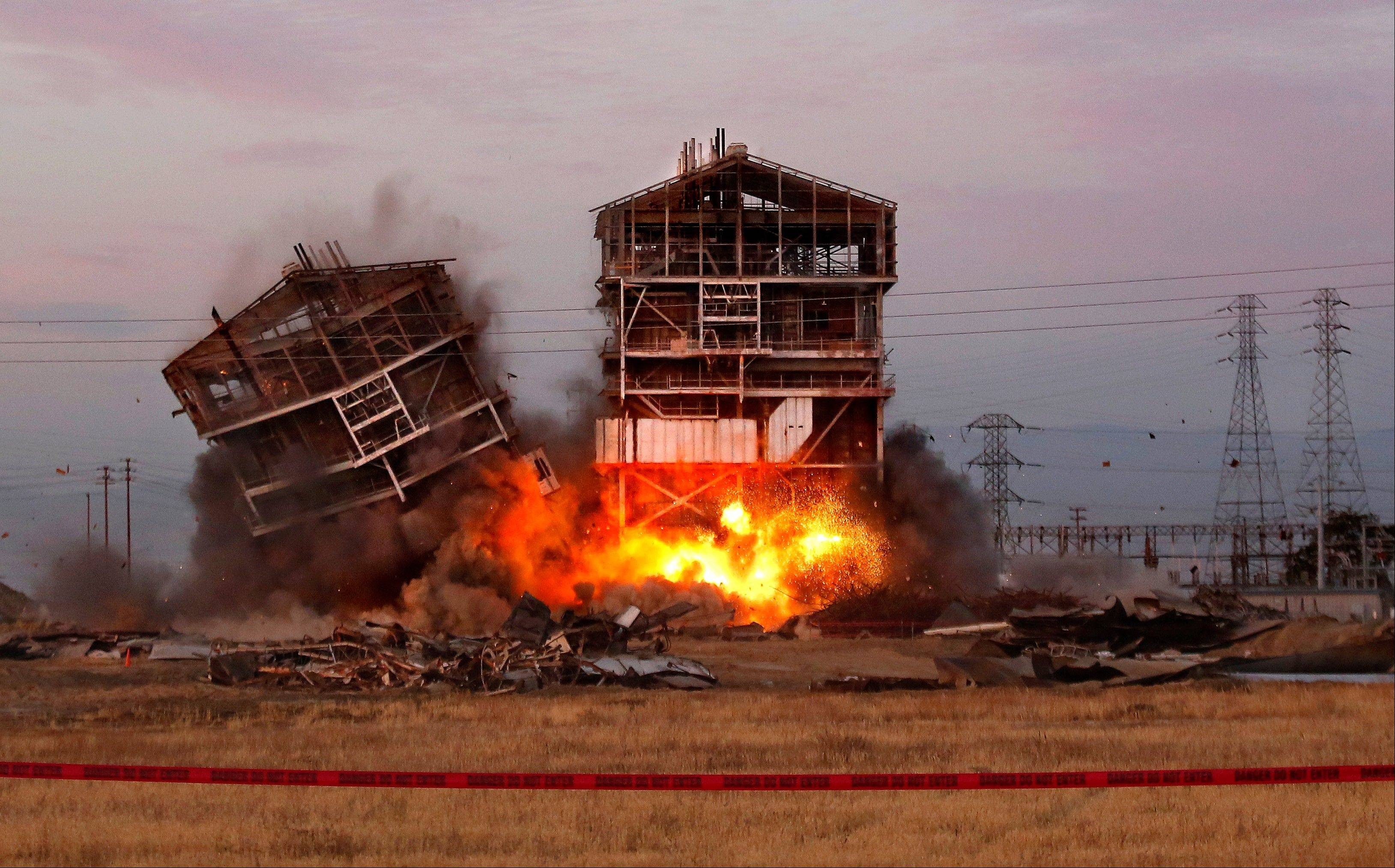 An explosion knocks down one of the remaining towers Saturday at the old Kern Power Plant, in Bakersfield, Calif.