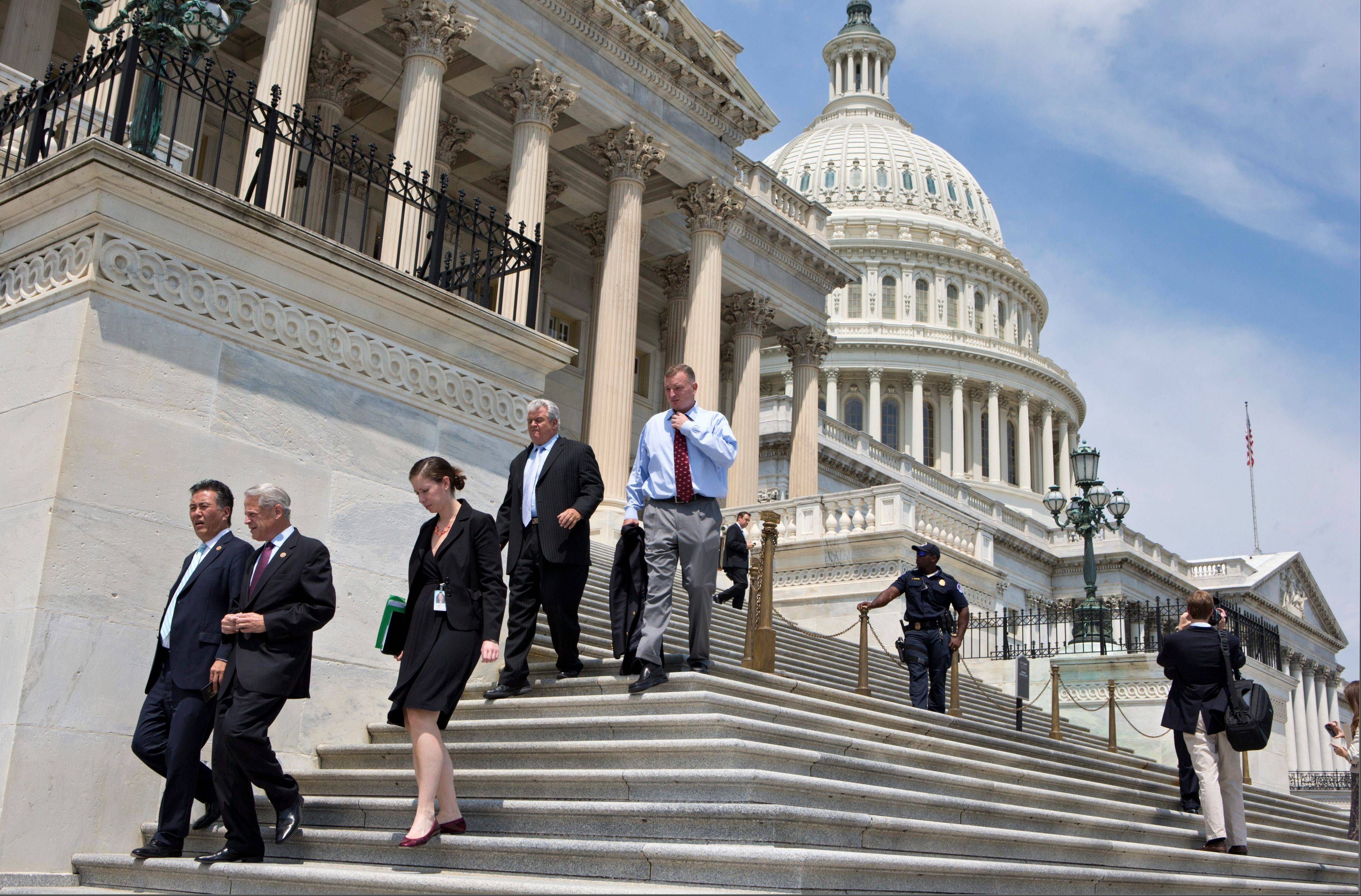 After final votes were cast, members of Congress walk down the steps of the House of Representatives Friday on Capitol Hill in Washington as they leave for a five-week recess.