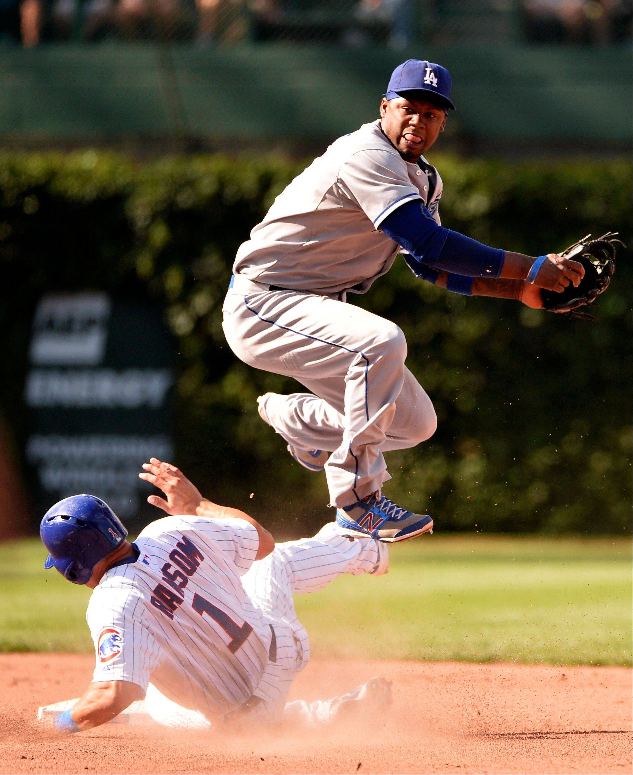 Dodgers shortstop Hanley Ramirez, right, leaps over Cody Ransom after turning a double play on a ground ball hit to second baseman Skip Schumaker by Darwin Barney.