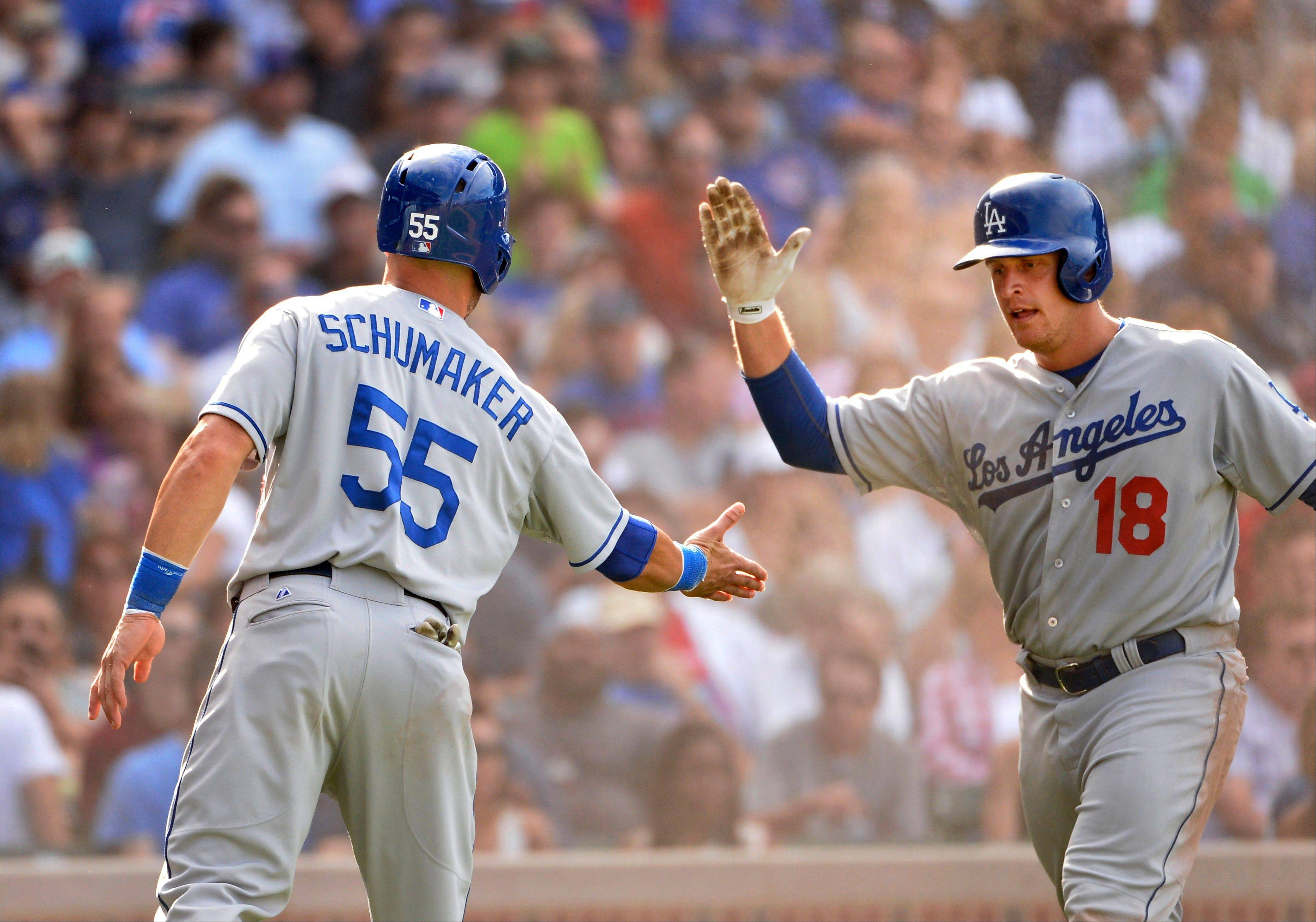 Los Angeles Dodgers' Tim Federowicz high-fives Skip Schumaker (55) after they scored on an RBI single hit by teammate Carl Crawford during the sixth inning of a baseball game against the Chicago Cubs, Saturday, Aug. 3, 2013, in Chicago.
