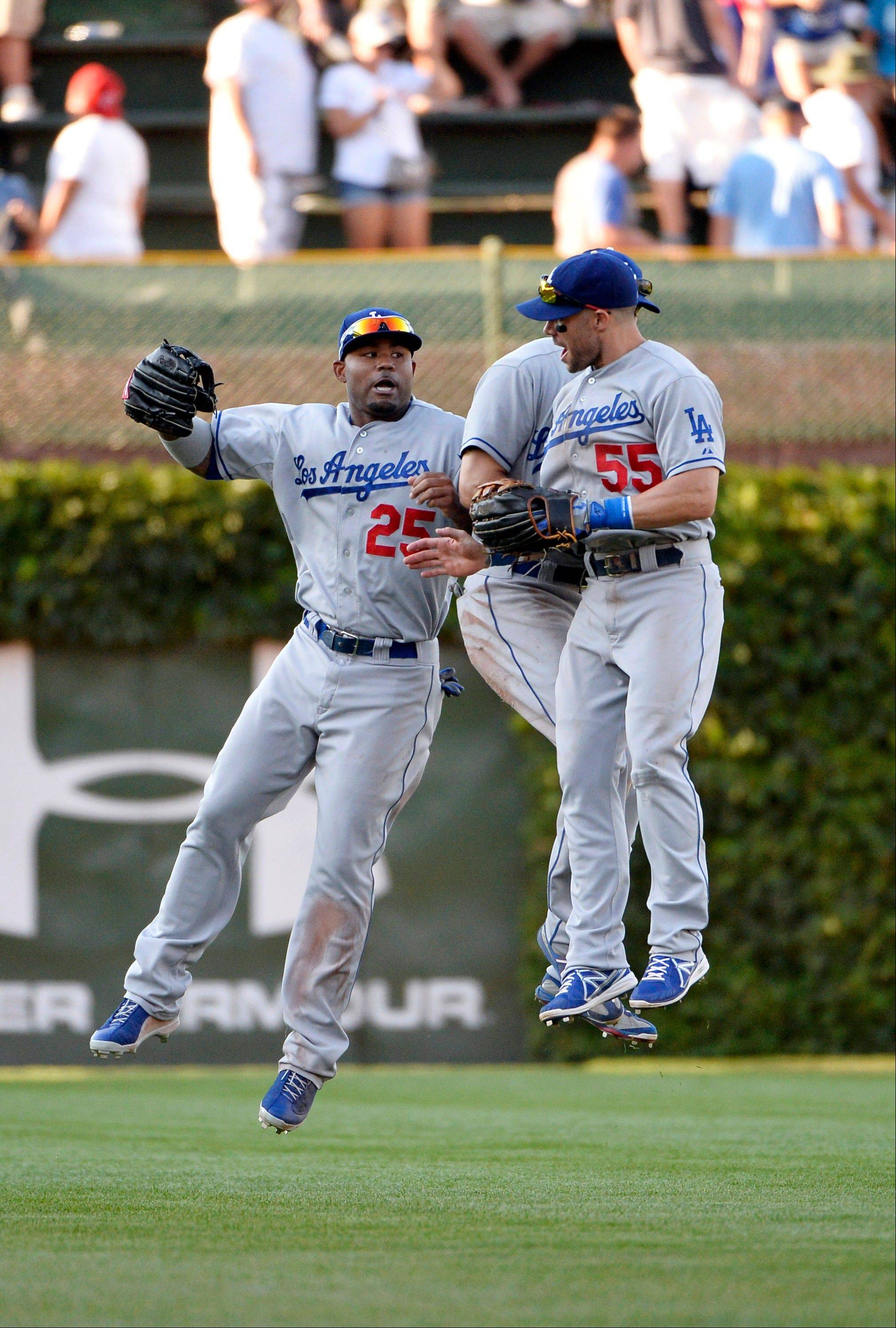 Los Angeles Dodgers outfielders Carl Crawford, left to right, Andre Ethier and Skip Schumaker celebrate their win after a baseball game against the Chicago Cubs, Saturday, Aug. 3, 2013, in Chicago. The Dodgers won 3-0.