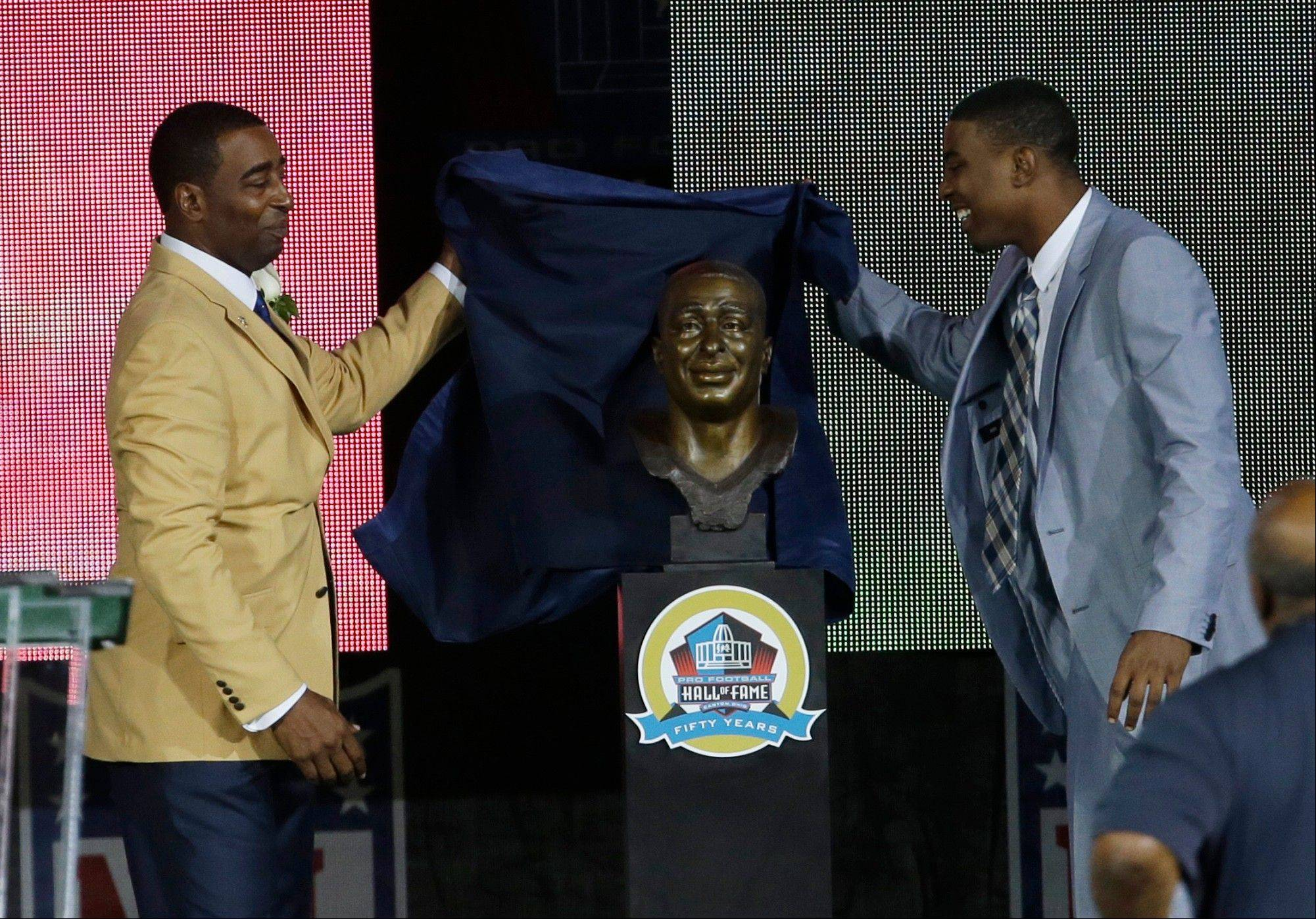 Former NFL football player Cris Carter, left, and his son, Duron, unveil Carter's bust during the induction ceremony at the Pro Football Hall of Fame Saturday in Canton, Ohio.