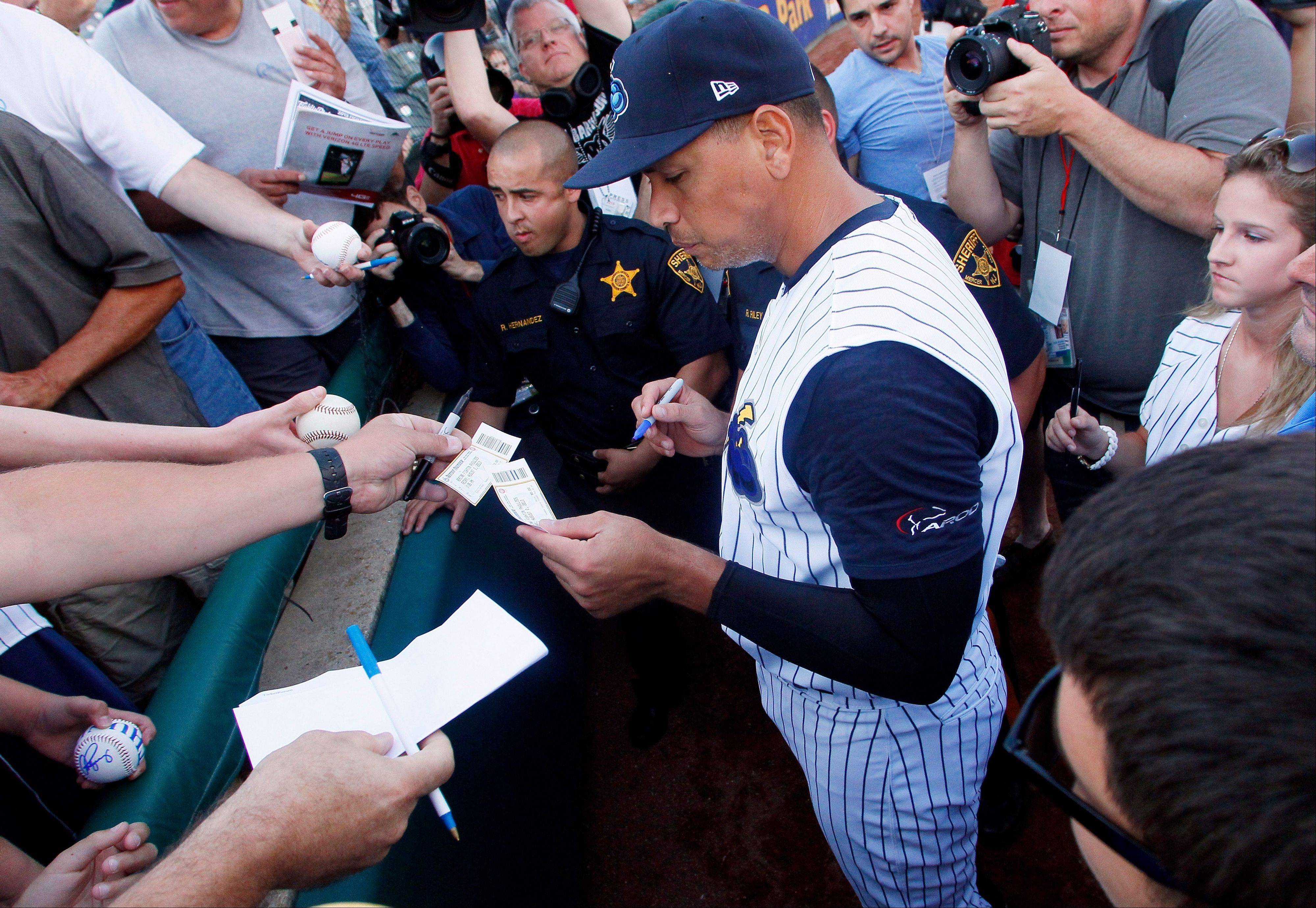 New York Yankees' Alex Rodriguez autographs a ticket stub for a fan before the start of a Class AA baseball game with the Trenton Thunder against the Reading Phillies, Friday, Aug. 2, 2013, in Trenton, N.J.
