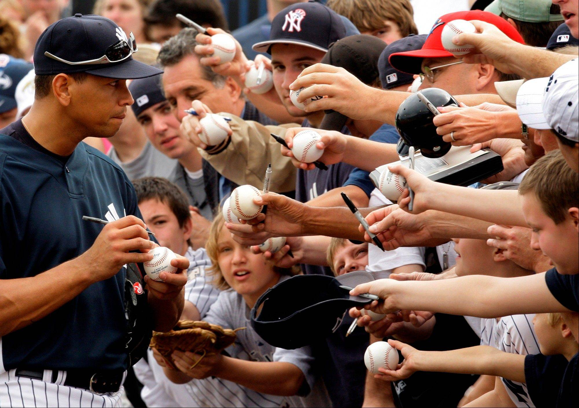 FILE - In this Feb. 19, 2009, file photo, New York Yankees' Alex Rodriguez, left, signs autographs during a spring training baseball workout in Tampa, Fla. Three MVP awards, 14 All-Star selections, two record-setting contracts and countless controversies later, A-Rod is the biggest and wealthiest target of an investigation into performance-enhancing drugs, with a decision from baseball Commissioner Bud Selig expected on Monday, Aug. 5, 2013.
