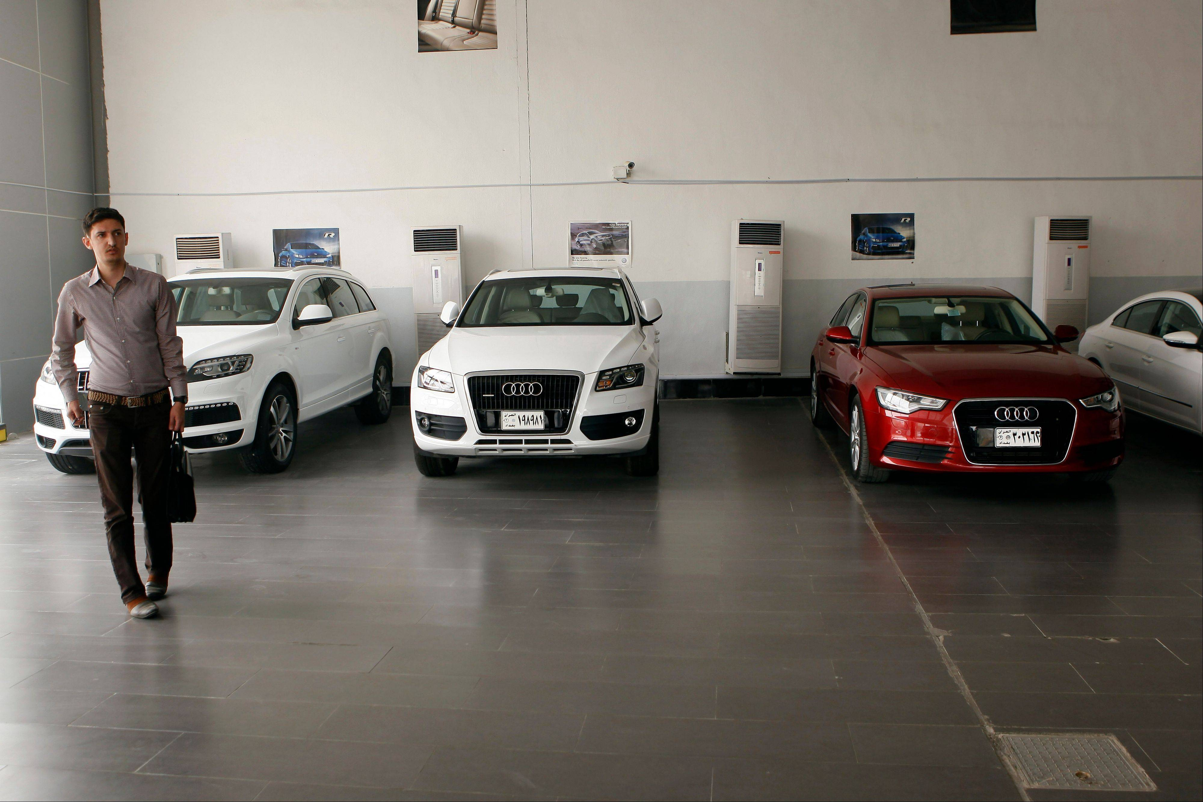 New Audi cars are seen at an automobile dealer in Baghdad, Iraq. A spike in violence is spilling over to Iraq�s struggling economy, with an increasingly murky future making customers reluctant to spend and the re-emergence of sectarian threats forcing costly changes to the way business is done.