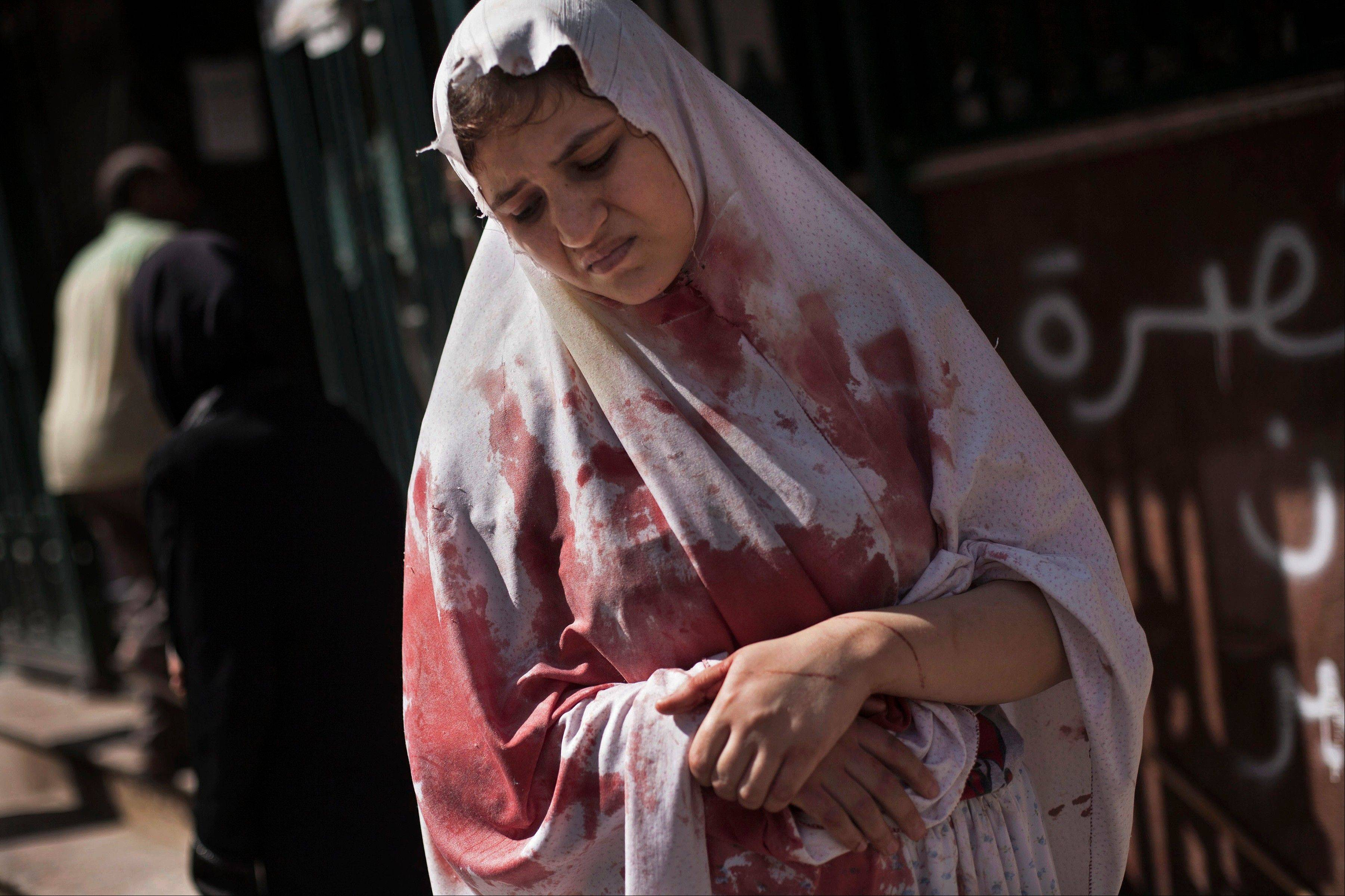 A wounded woman still in shock leaves Dar El Shifa hospital in Aleppo, Syria, last September. The civil war has laid waste to the country�s cities, shattered its economy and killed more than 100,000 people since March 2011.
