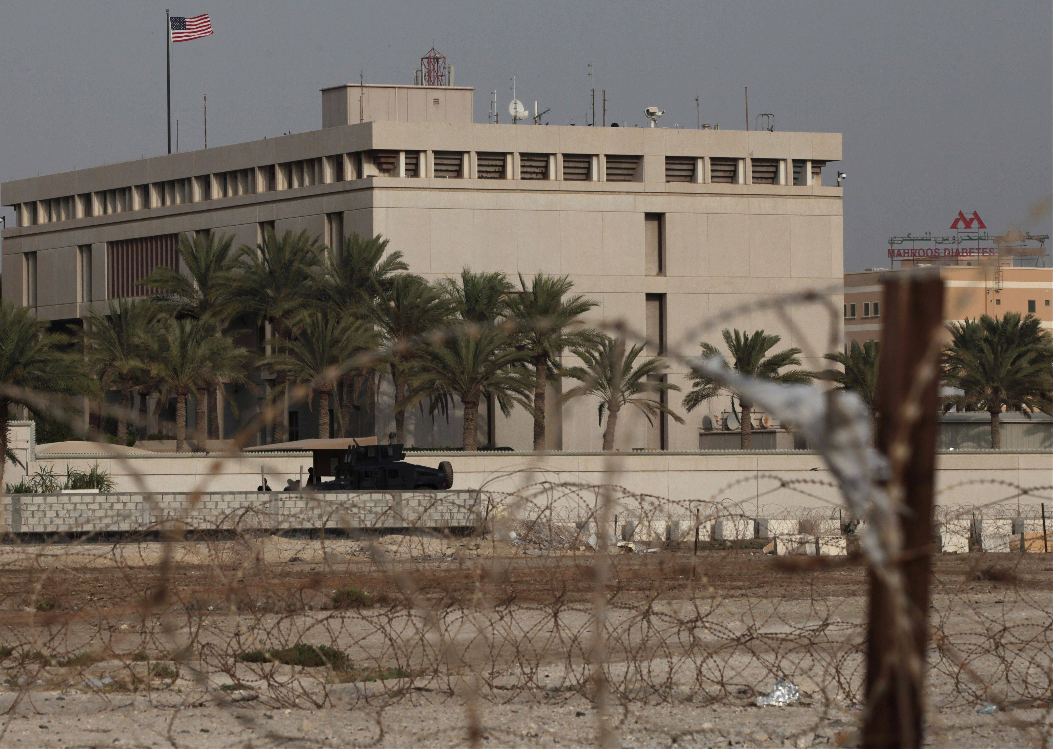 A Bahraini armored vehicle and personnel reinforce U.S. Embassy security just outside of a gate to the building, surrounded in barbed wire, in Manama, Bahrain, on Sunday.