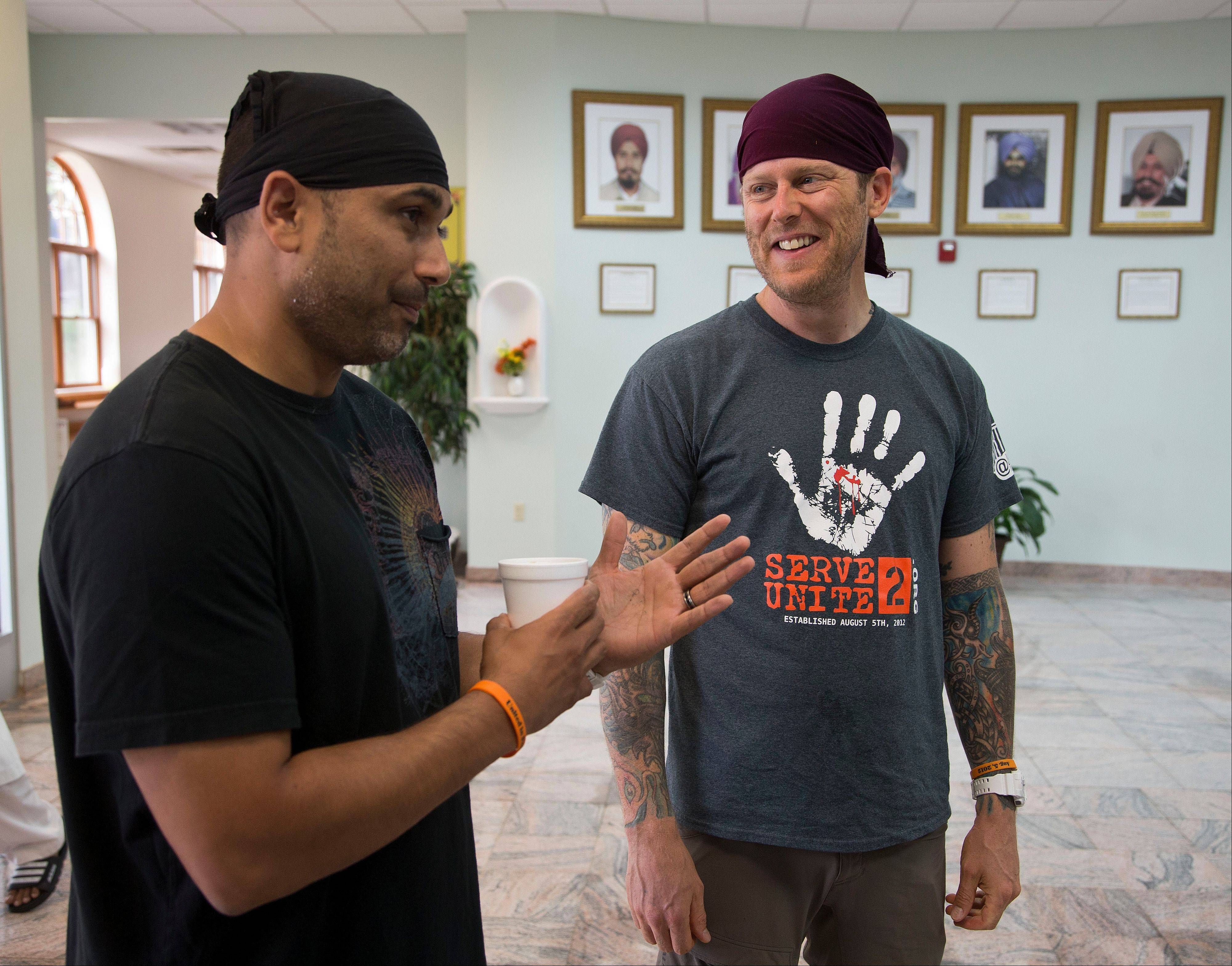 Pardeep Kaleka, left, and Arno Michaelis talk at the Sikh Temple of Wisconsin in Oak Creek, Wis. A year ago a white supremacist shot and killed six temple members, including Kaleka�s father.