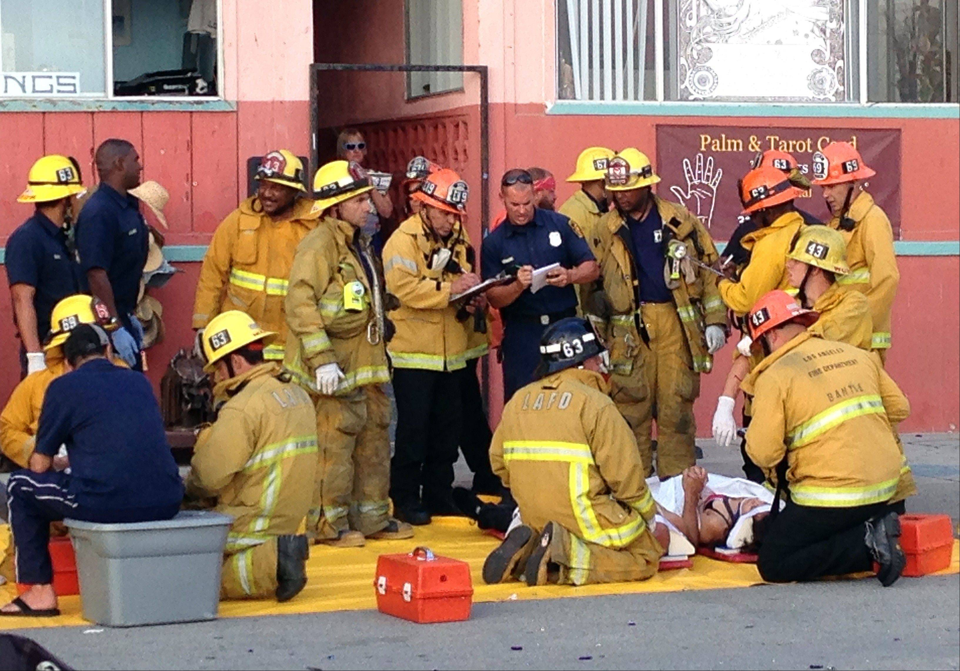 Police and firefighters assist an injured pedestrian at the scene where a car drove through a packed afternoon crowd along the Venice Beach boardwalk Saturday in Los Angeles. One woman was killed.