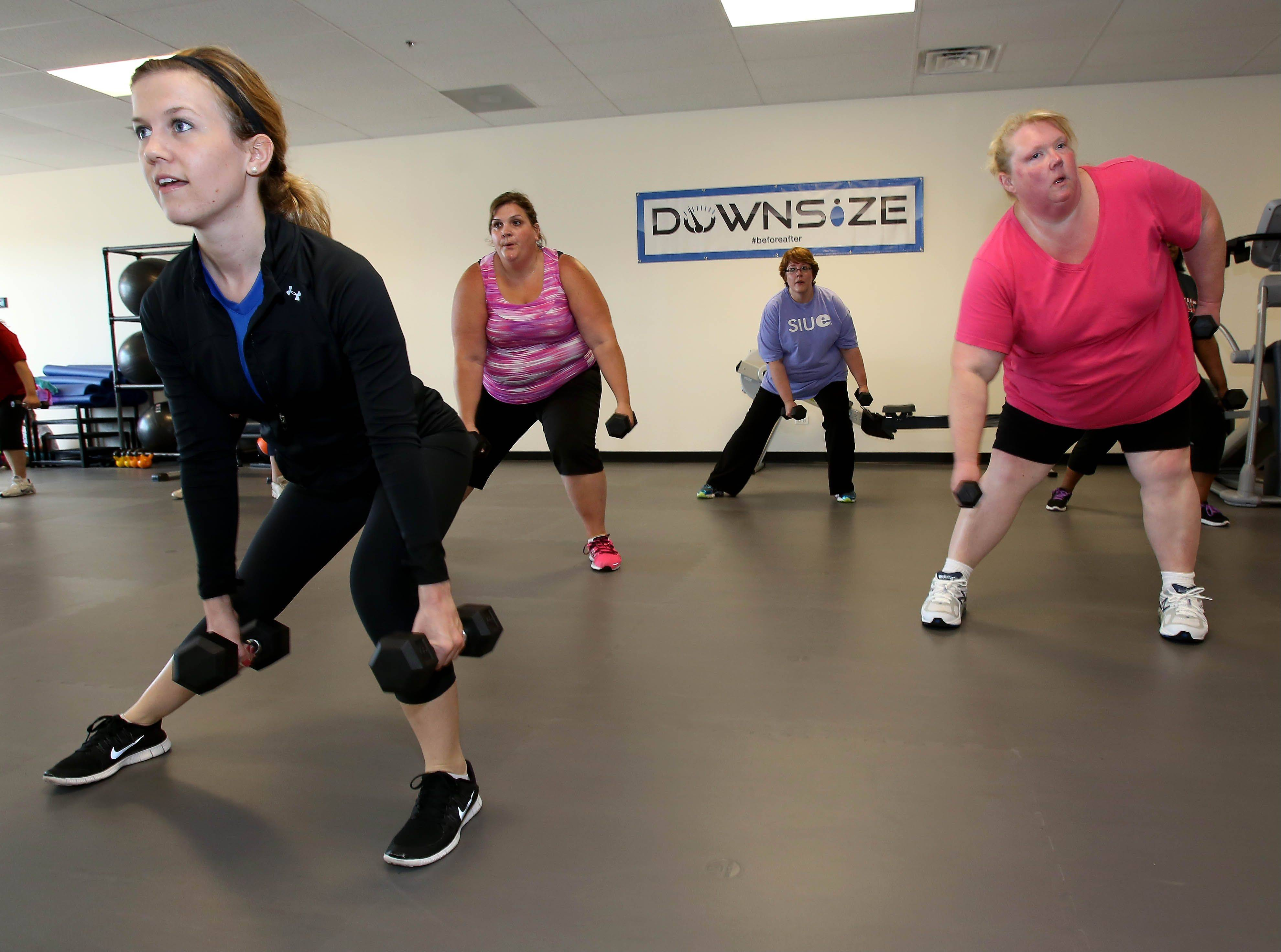 "Trainer Jillian McAfee leads Genie Przybylski of Oswego, Diane Reiter of Aurora, and Kim Tremblay of Bolingbrook in a circuit training class at Downsize Fitness' new gym in Naperville. One of four locations of ""the world's first overweight-only gym,"" the Naperville facility opened July 1 at 1960 Springbrook Square Drive, Suite 104."