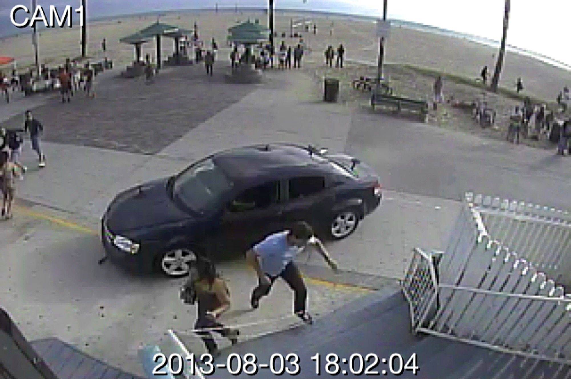 In this image take from a security camera, pedestrians scatter as a car drives through a packed afternoon crowd along the Venice Beach boardwalk Saturday in Los Angeles. At least a dozen people were injured, and one of them died later at the hospital, according to police.