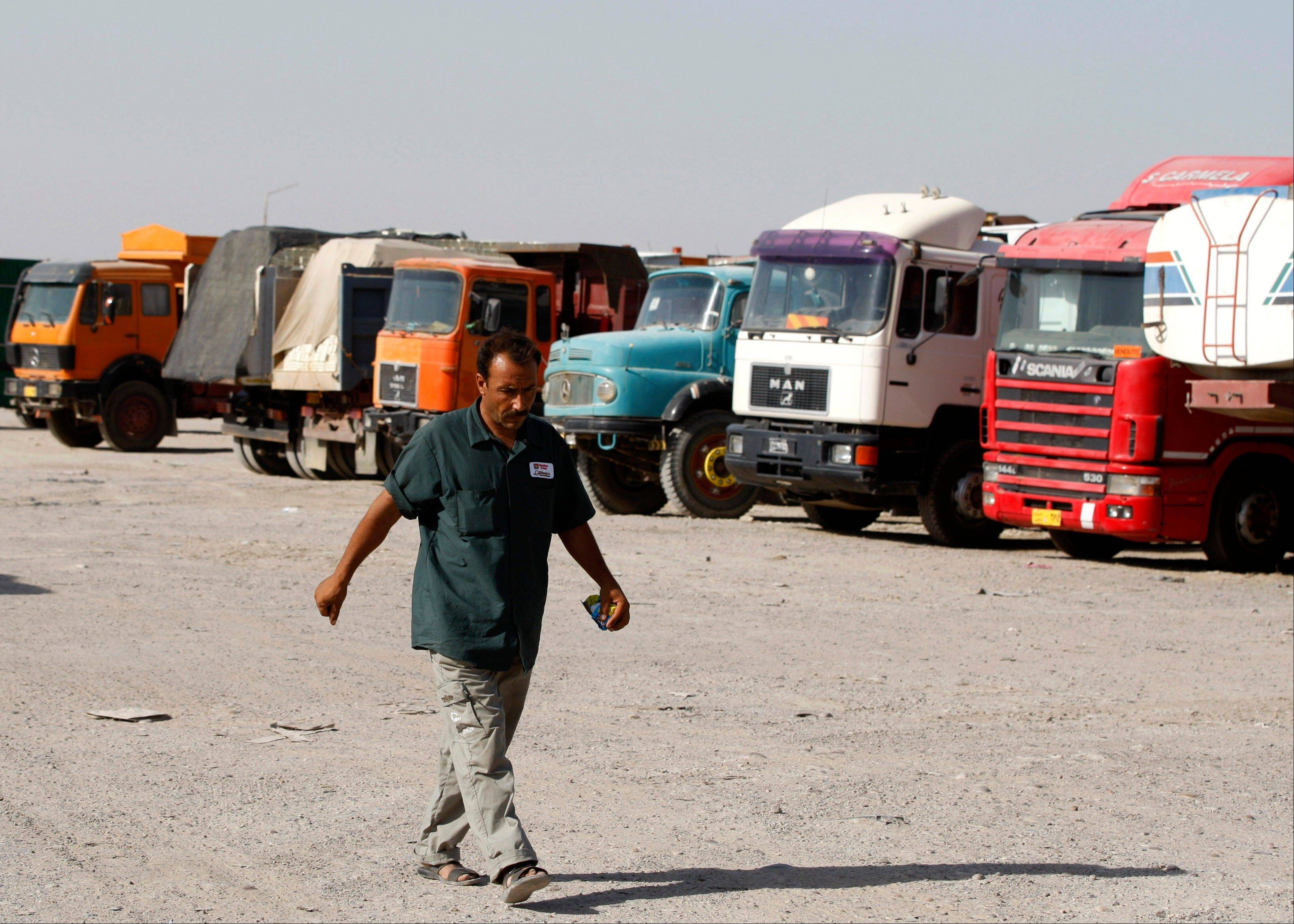 A truck driver walks past trucks in a truck yard in the capital's western Sunni-dominated Ghazaliyah neighborhood. A spike in violence is spilling over to Iraq's struggling economy, with an increasingly murky future making customers reluctant to spend and the re-emergence of sectarian threats forcing costly changes to the way business is done.