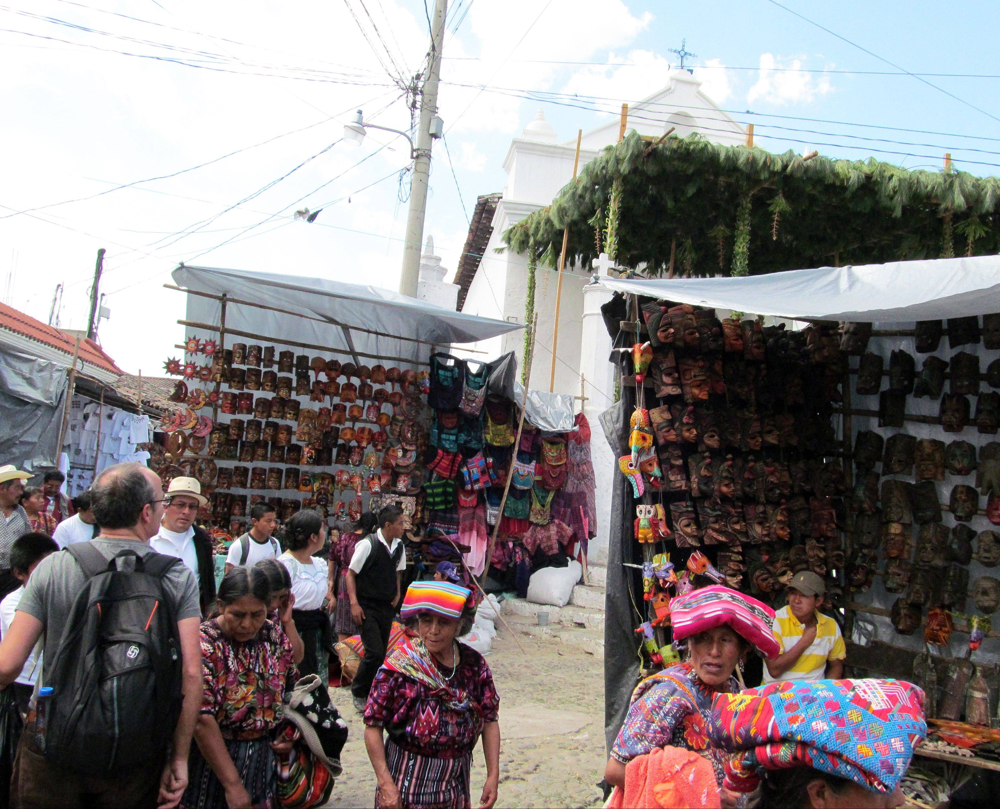 Mayan women sell colorful Guatemalan fabrics in front of market stalls in Chichicastenango, Guatemala. Chichicastenango is also famed for its expansive local crafts market.