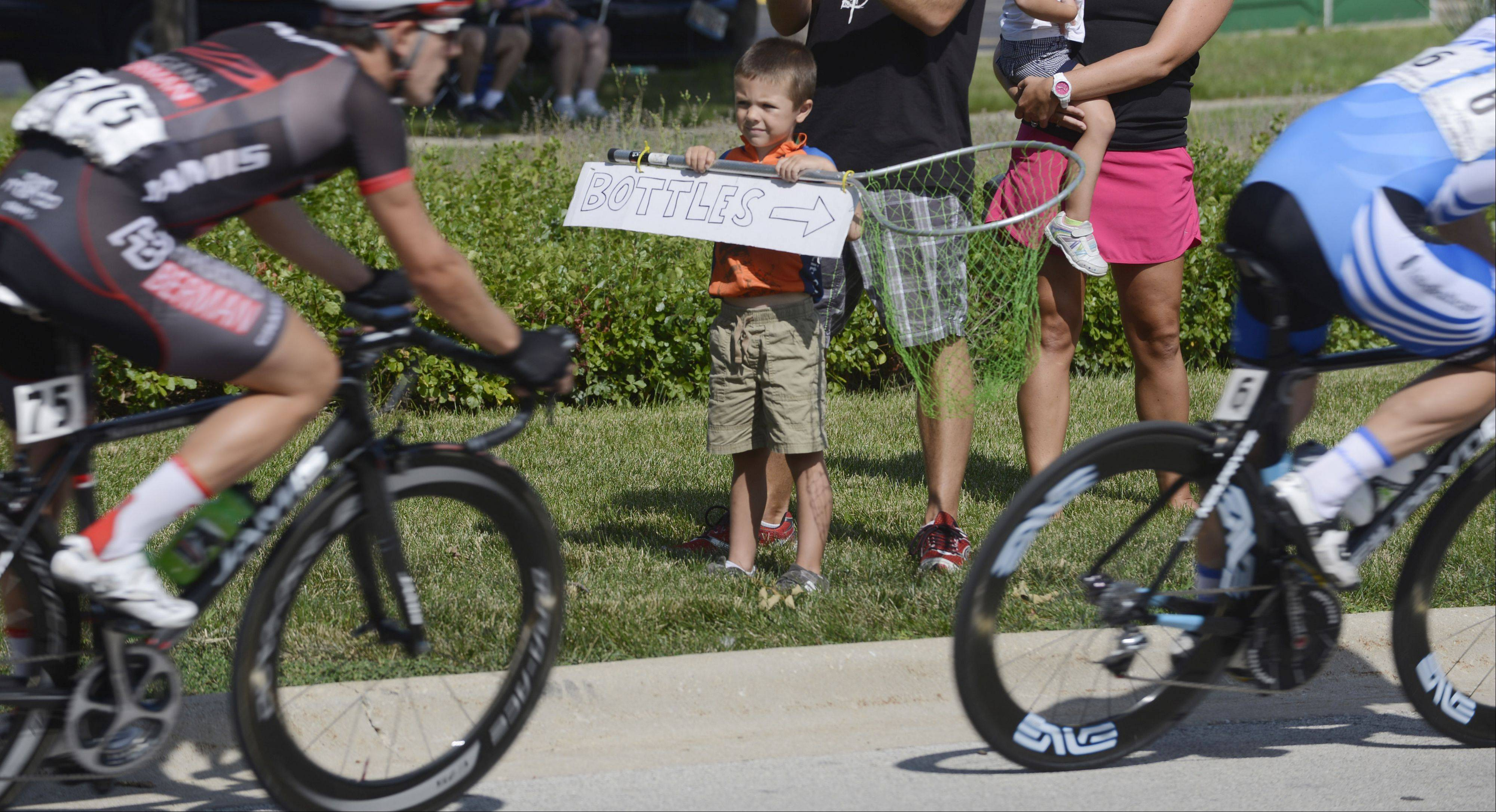 Sean McCammon, 5, of Minooka holds up a net and sign for rider's water bottles as cyclists compete in the Gullo International Pro Men Circuit Race, Stage 3, during the Tour of Elk Grove Sunday.