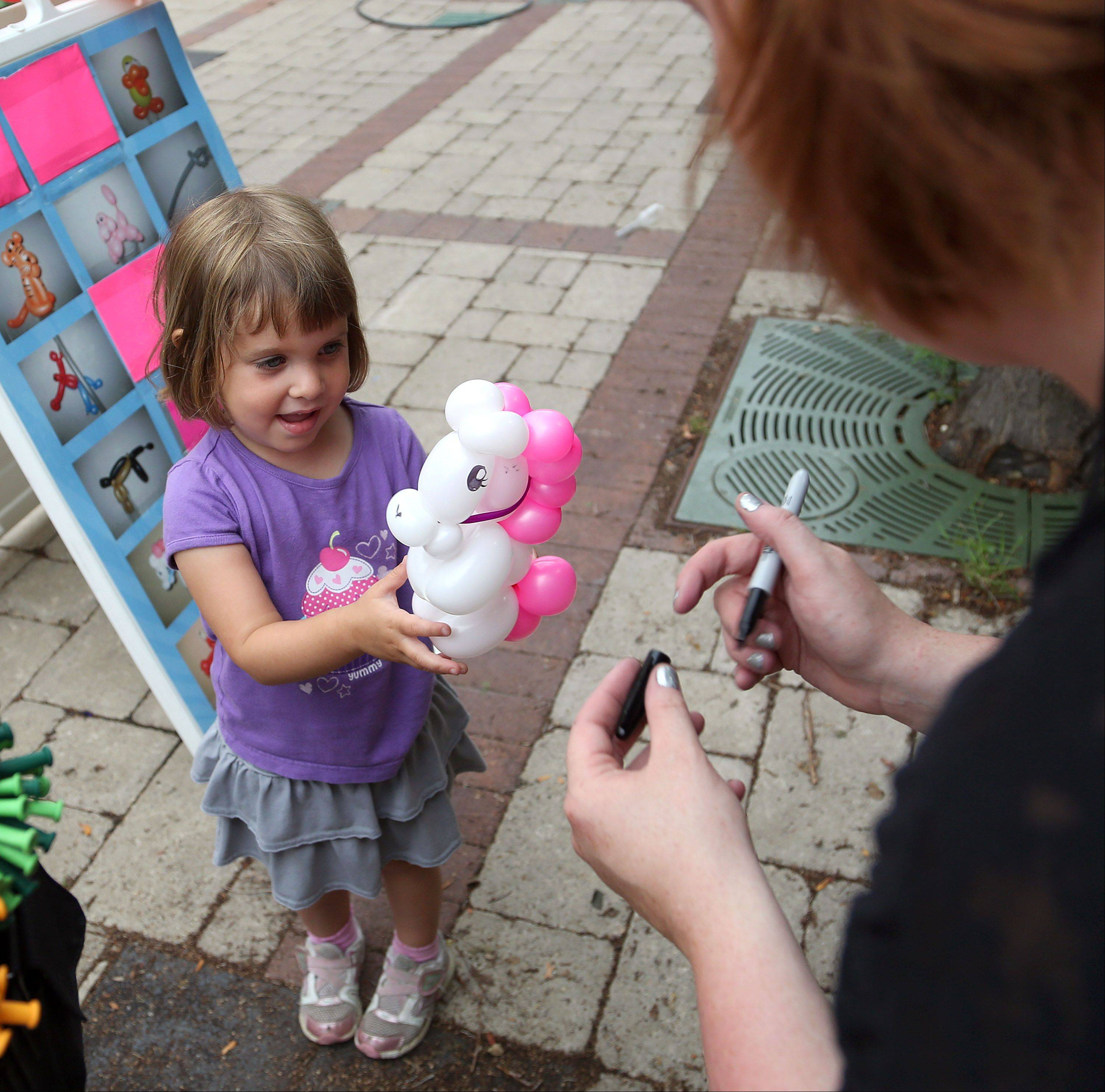 Lauren Miller, 3, of Grayslake, gets a balloon animal made by Amber Burkey, of Winthrop Harbor, as Grayslake held it's weekly farmers market.