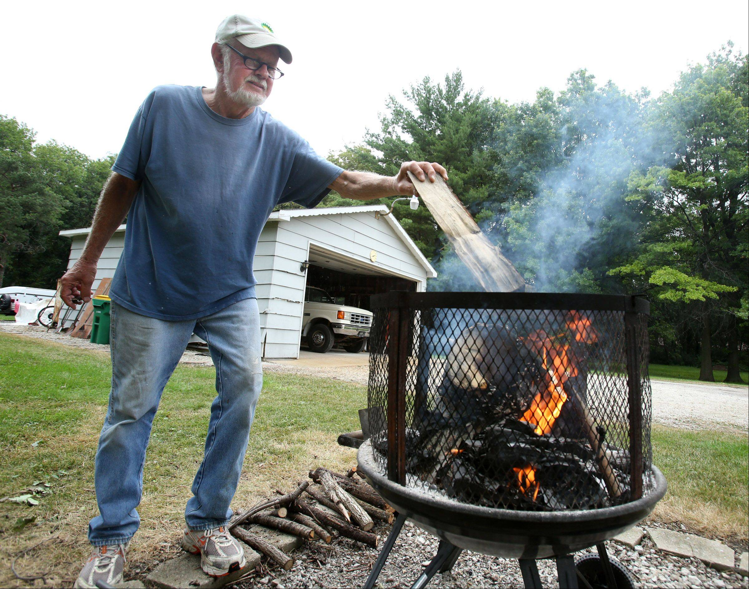WP McRaven places small branches, from a tree he cut down earlier in the year, on an enclosed fire pit in his Wheeling backyard Wednesday. McRaven said he was burning the wood because he likes the smell while working in his yard, but admits he wouldn't be burning the wood if it was above 80 degrees.