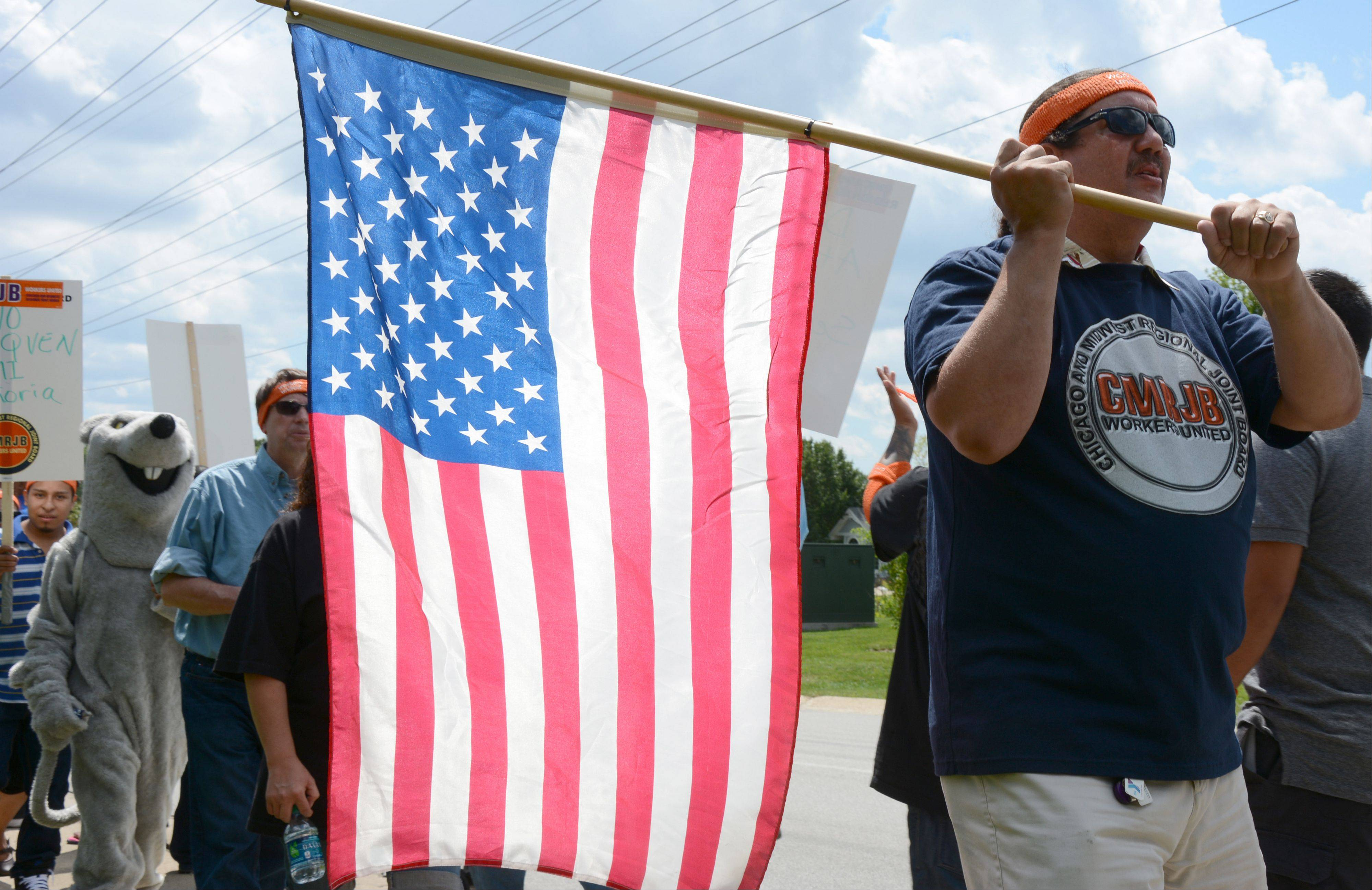 Southwest Area Director for Workers United, John Lacey, carries an American flag during a rally at Grecian Foods Thursday.