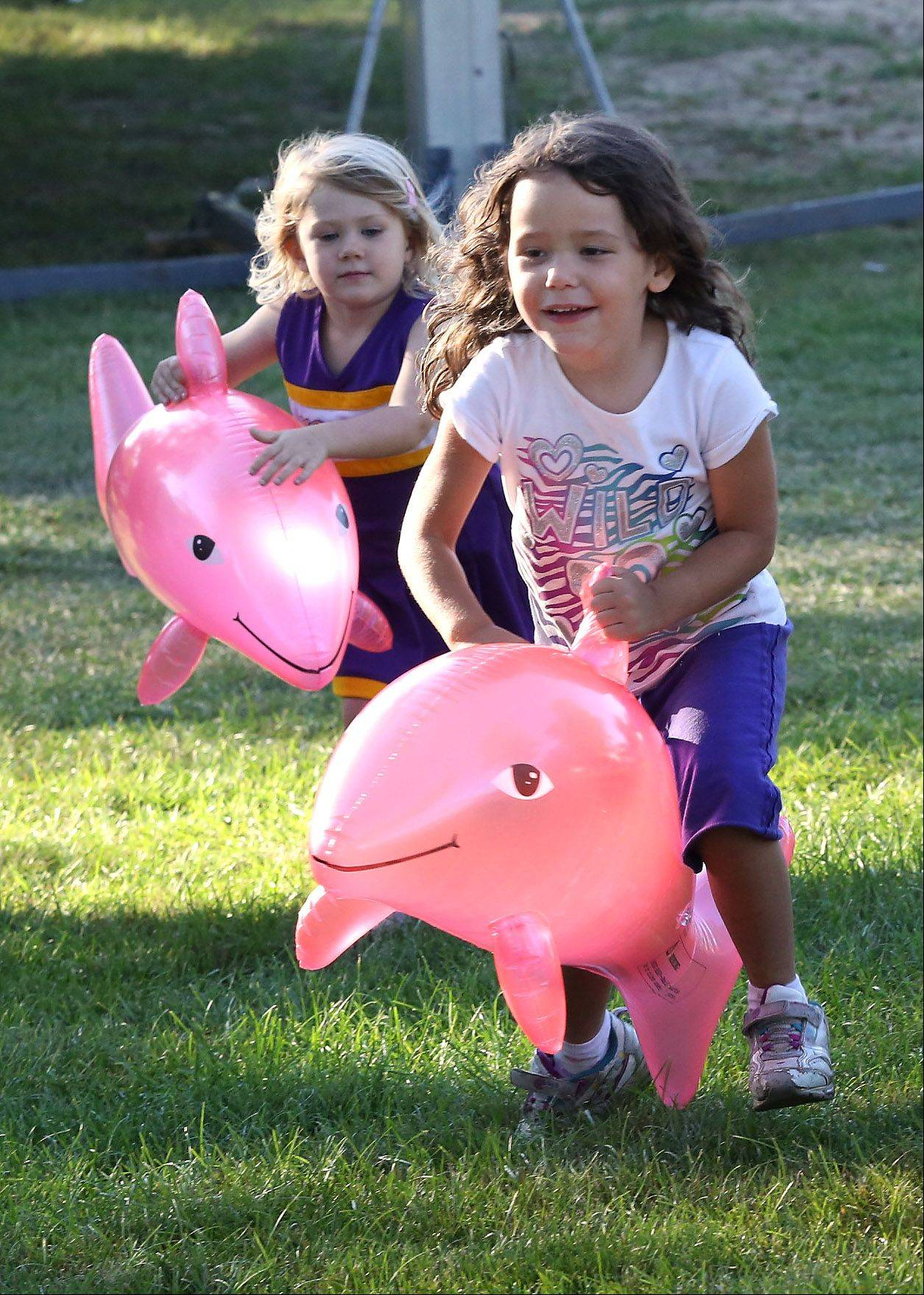 Jade Stles, 5, right, and Payton Rollene, 3, both of Lake Villa play with dolphins that they won at the Inflate Game in the amusement park during the first day of the Lake Villa Days festival Thursday at Lehmann Park. The festival featured games, food, rides and games.
