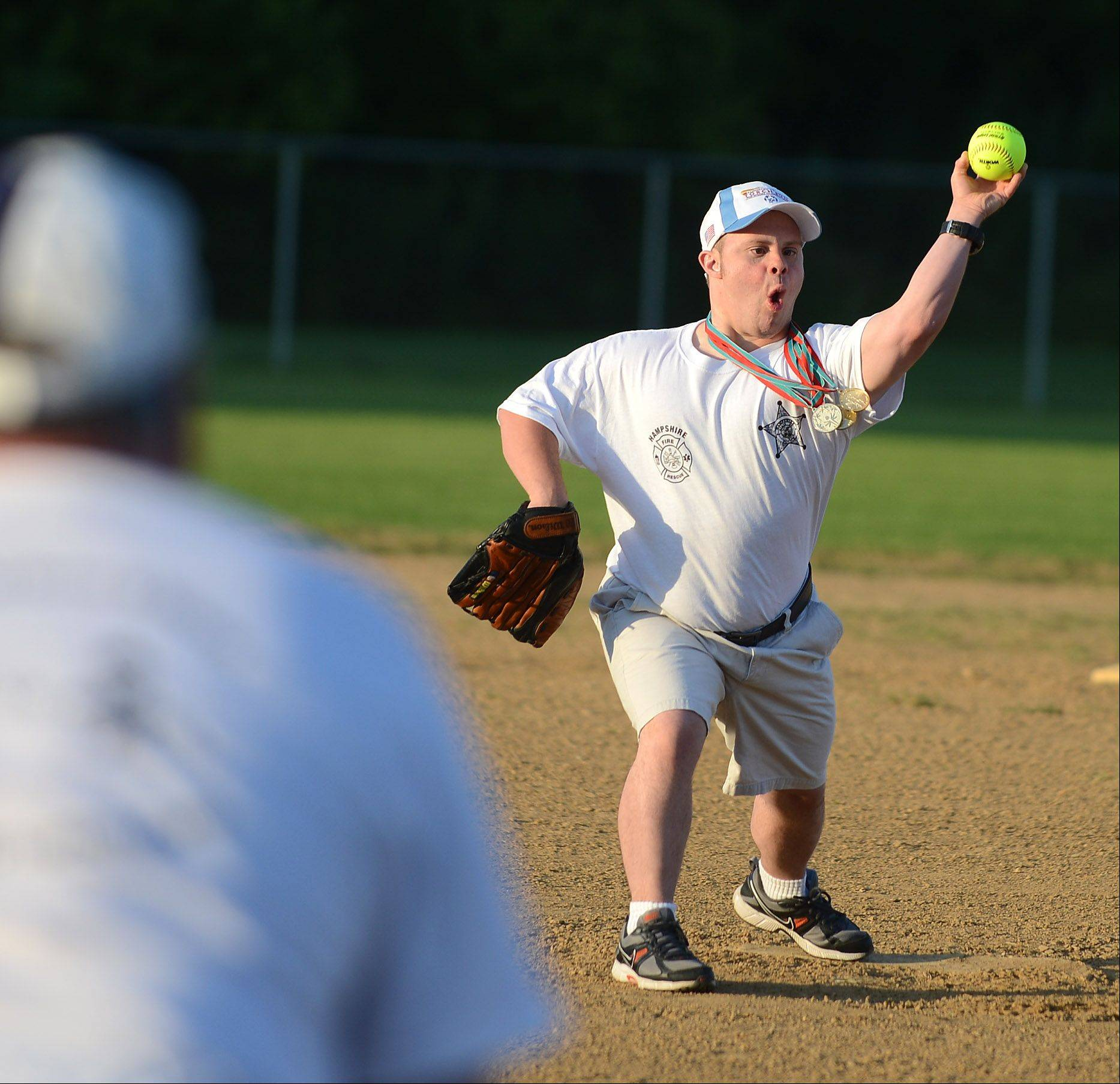 Special Olympian Dustin Dickens of Sugar Grove throws out the ceremonial first pitch before the annual Guns and Hoses charity softball game at Hampshire's Coon Creek Country Days festival Thursday. The game raises money for Illinois Special Olympics.