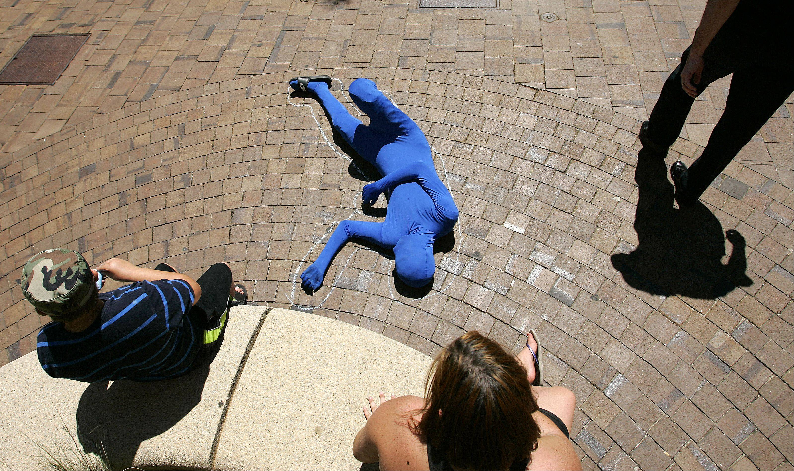 Fifteen-year-old Mason Keys has some fun with people as they pass by while wearing his blue suit Saturday during Art & Soul on the Fox in Elgin.