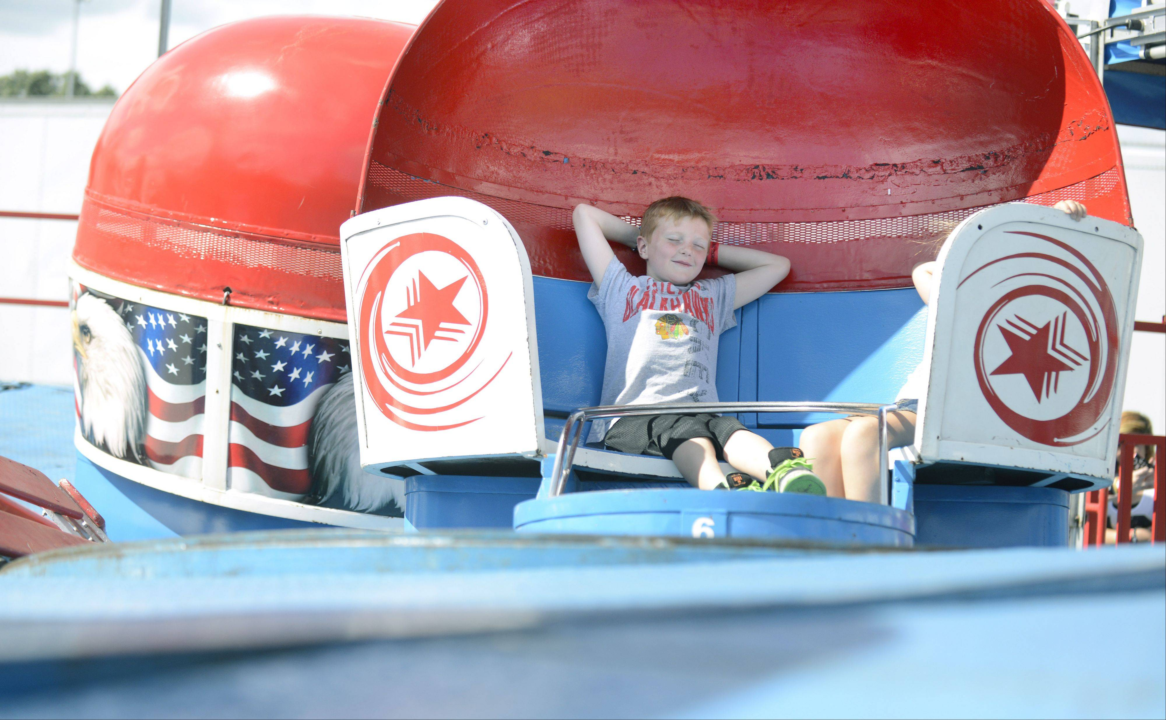 Connor Harvey reclines while spinning on the Tilt-a-Whirl ride with Lily Engelhardt, both 7 and from Hampshire, at Hampshire's Coon Creek Days on Saturday, August 3. Connor comes to Coon Creek Days every year.