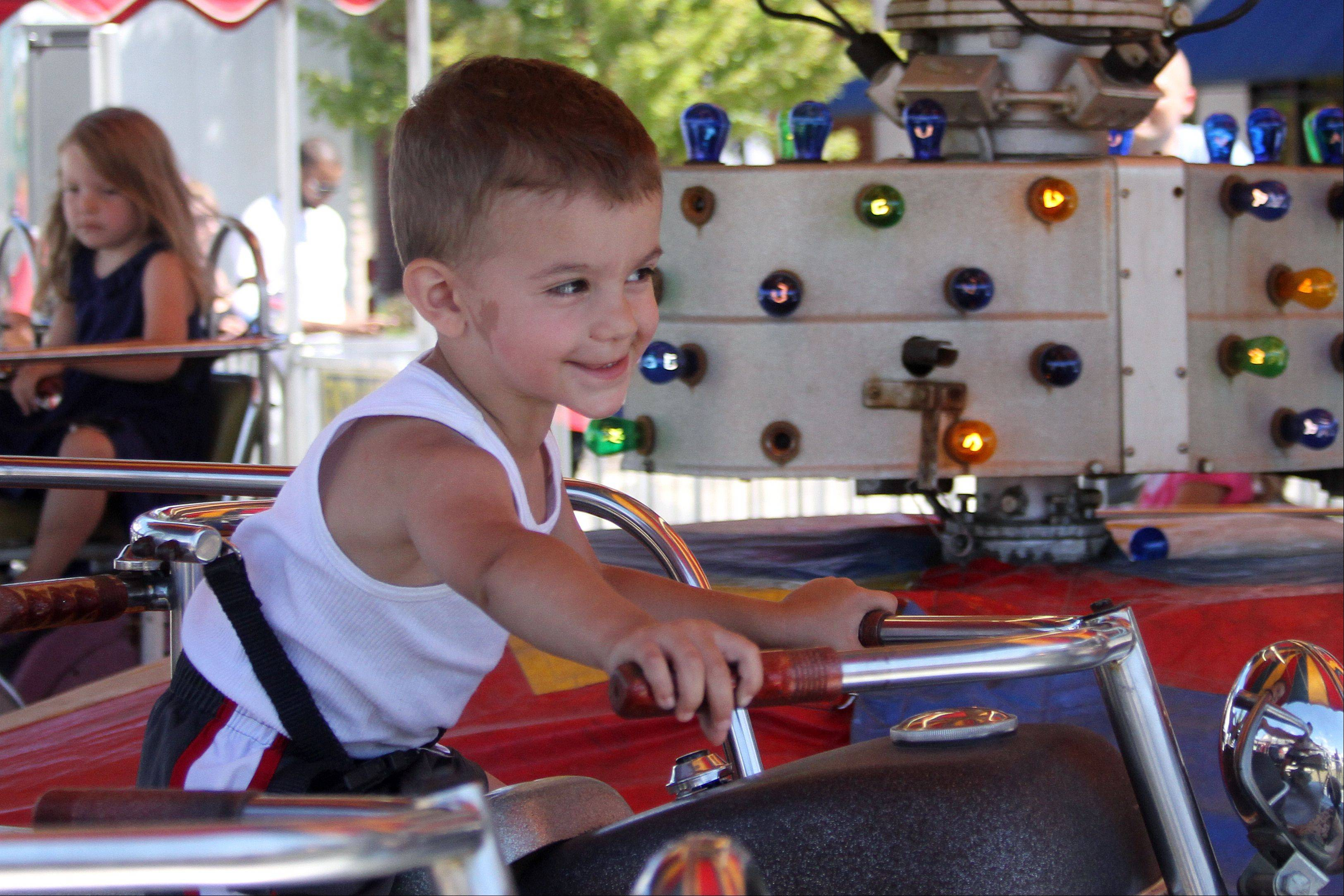 Vincenzo Camarata, 2, of Roselle, rides a motorcycle at the 2013 Taste of Roselle on Saturday, August 3, 2013. The three-day festival opened Friday and ends Sunday.