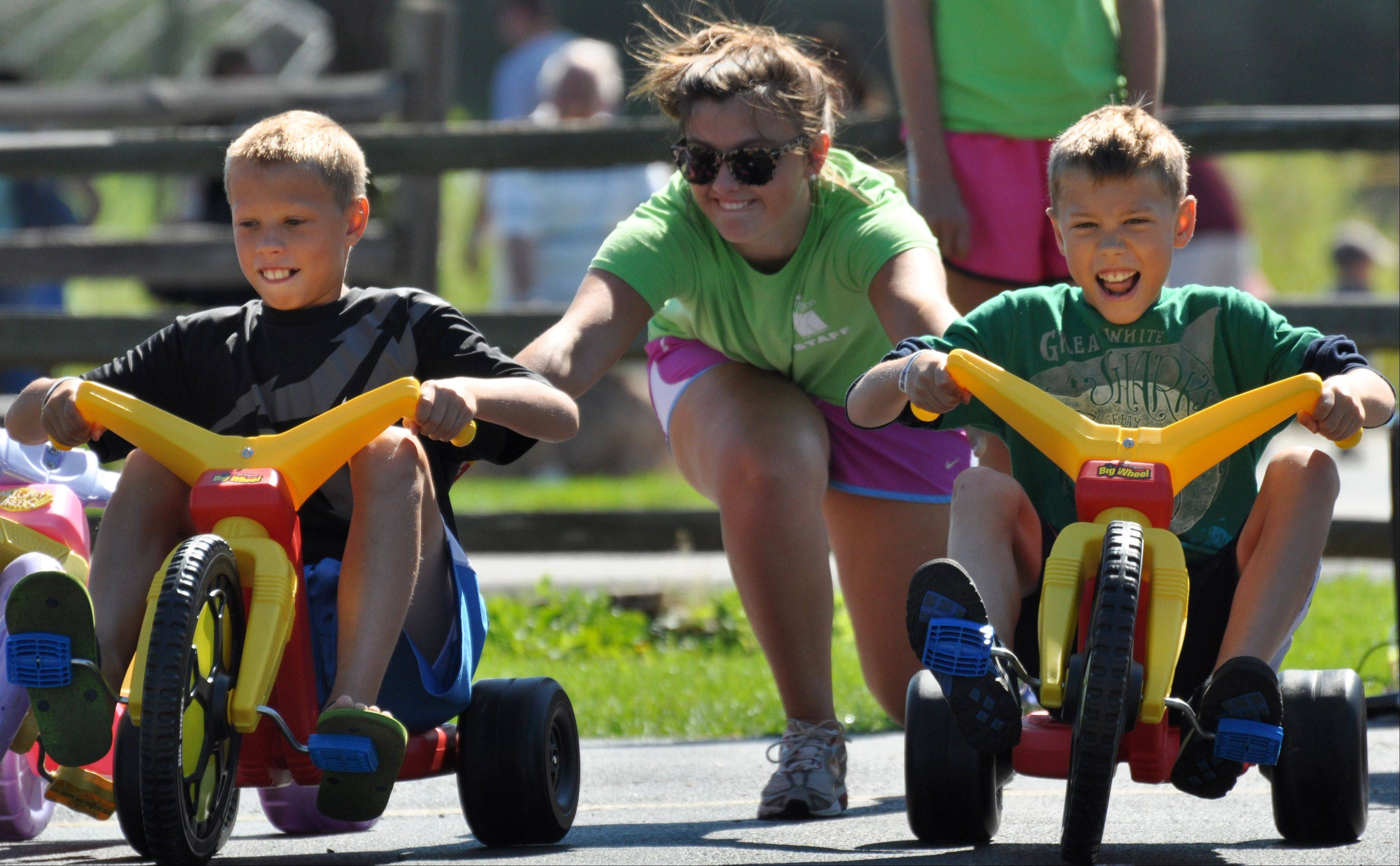 Left, David Krauklis, of Hampshire, and brother Johnny get a push start from volunteer Emma Raider, of Barrington during the 14th annual Big Trucks event in Barrington Saturday, August 3.