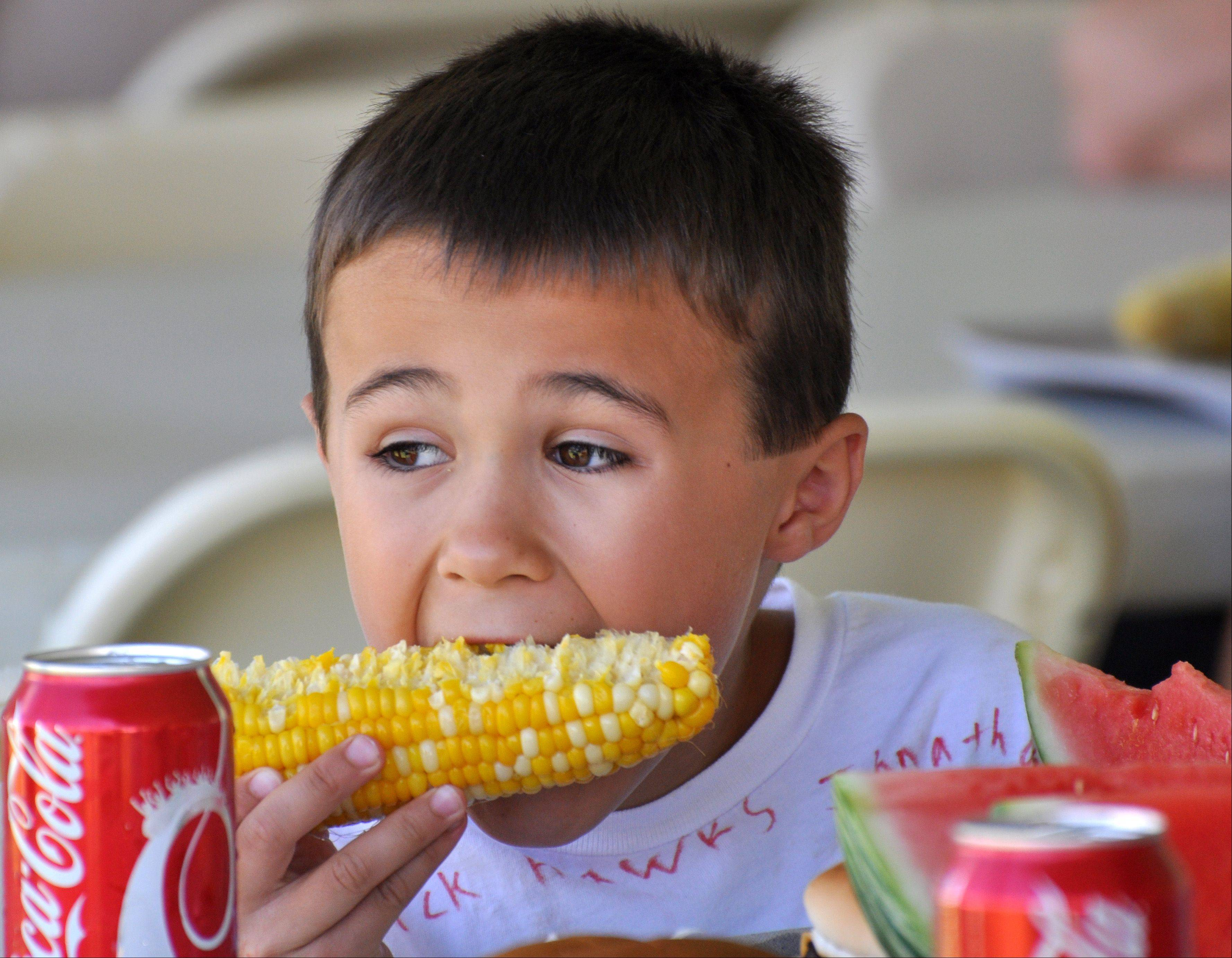 Drew Bhillibs, 7, of Arlington Heights, eats an ear of corn during the 57th annual Cornfest in Rolling Meadows Saturday, August 3.