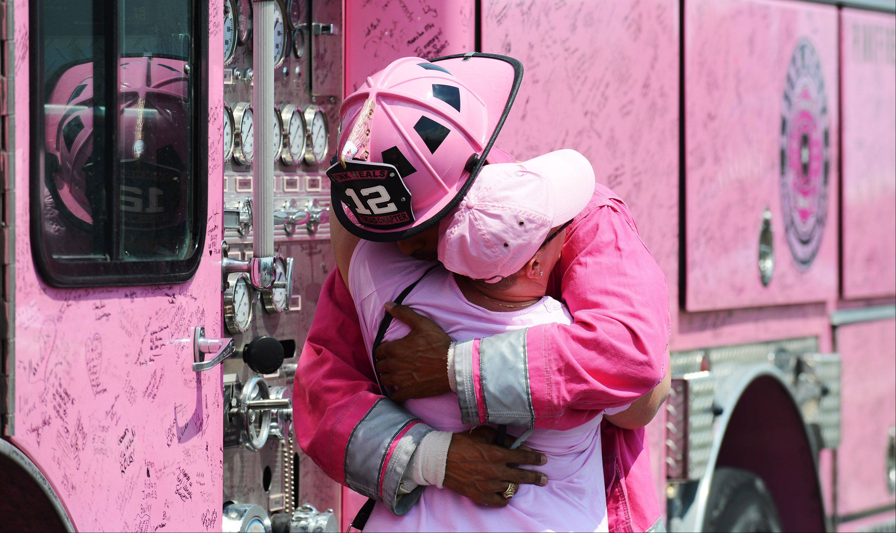Aileen Petersen of Union gets a hug from firefighter Chuck Goins who travels cross-country with the Pink Heals fire trucks. The organization stopped at Spring Hill Gymnastics in West Dundee to surprise some of their employees who are battling cancer on Friday, August 2.