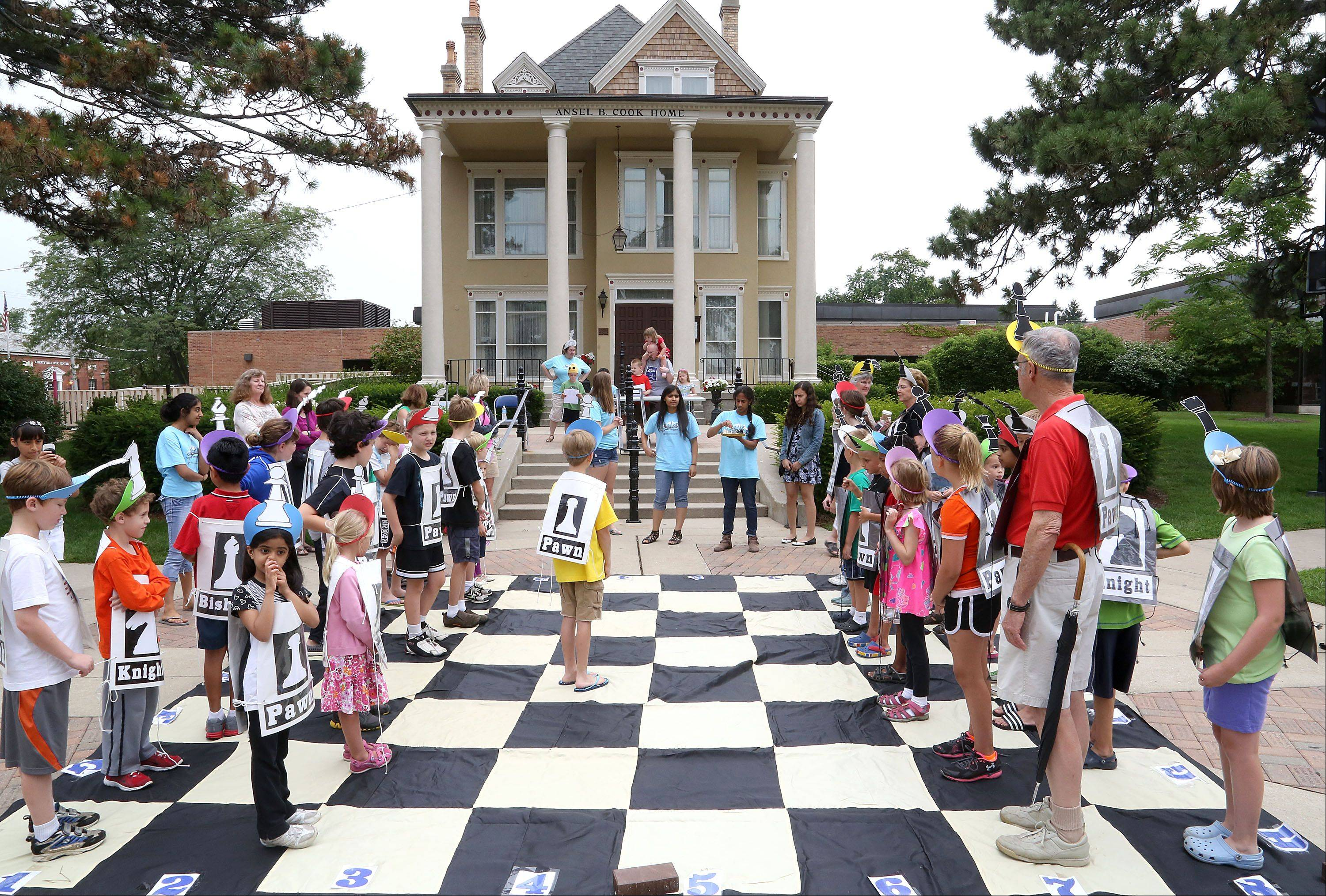 Kids take the role of chess pieces as Cook Park Library offered life-size chess in Cook Park in Libertyville Tuesday.
