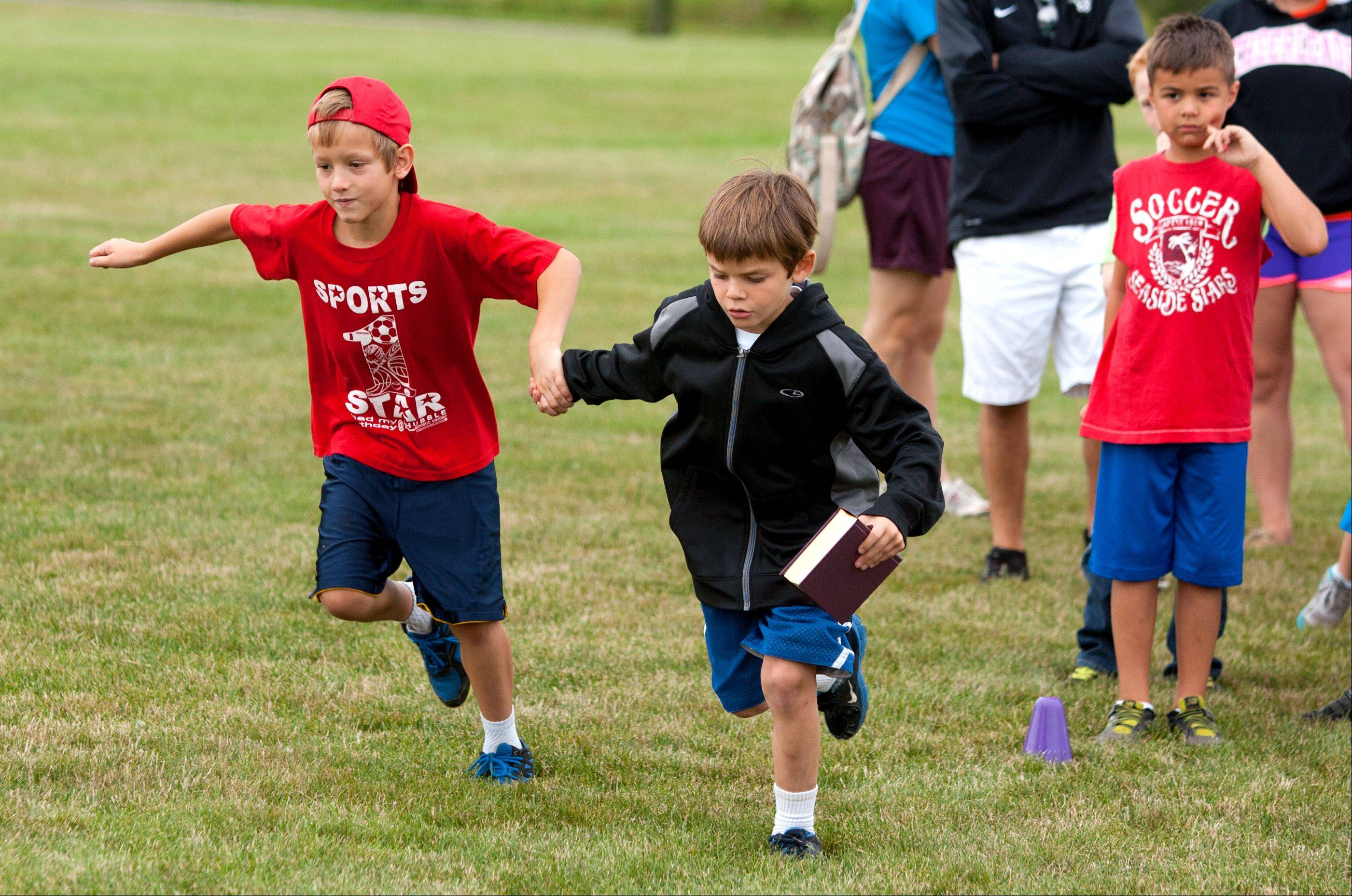 Noah Collingbourne, left, and Robert Barnhisel, right, both of the Winfield Park District, run in the precious cargo partner relay race during the fifth annual WAYS Salute to the Olympics, held at Carol Stream's Red Hawk Park.