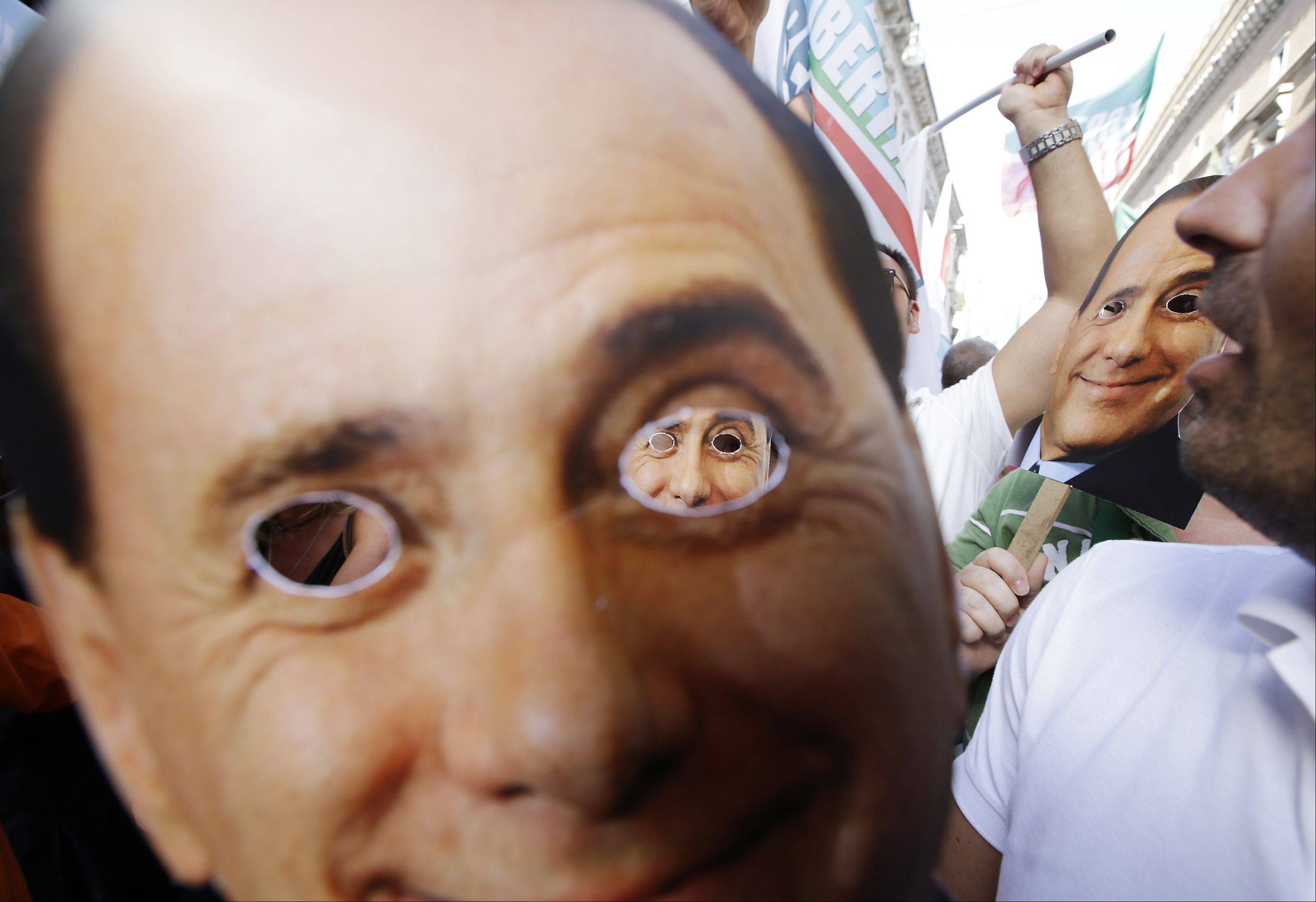 Supporters carry masks portraying Silvio Berlusconi during a demonstration Sunday in Rome.