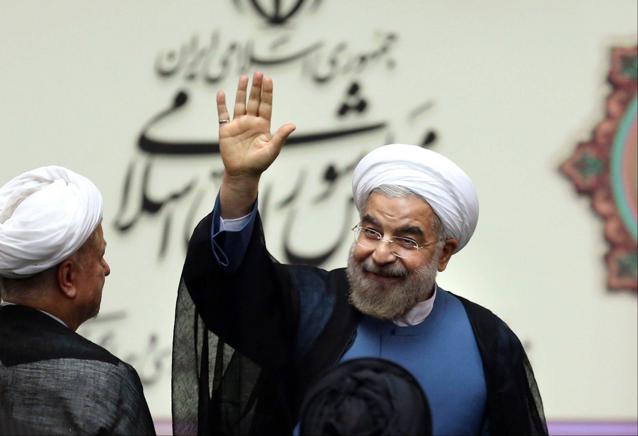 New Iranian President Hasan Rouhani waves after his swearing-in at the parliament Sunday in Tehran.