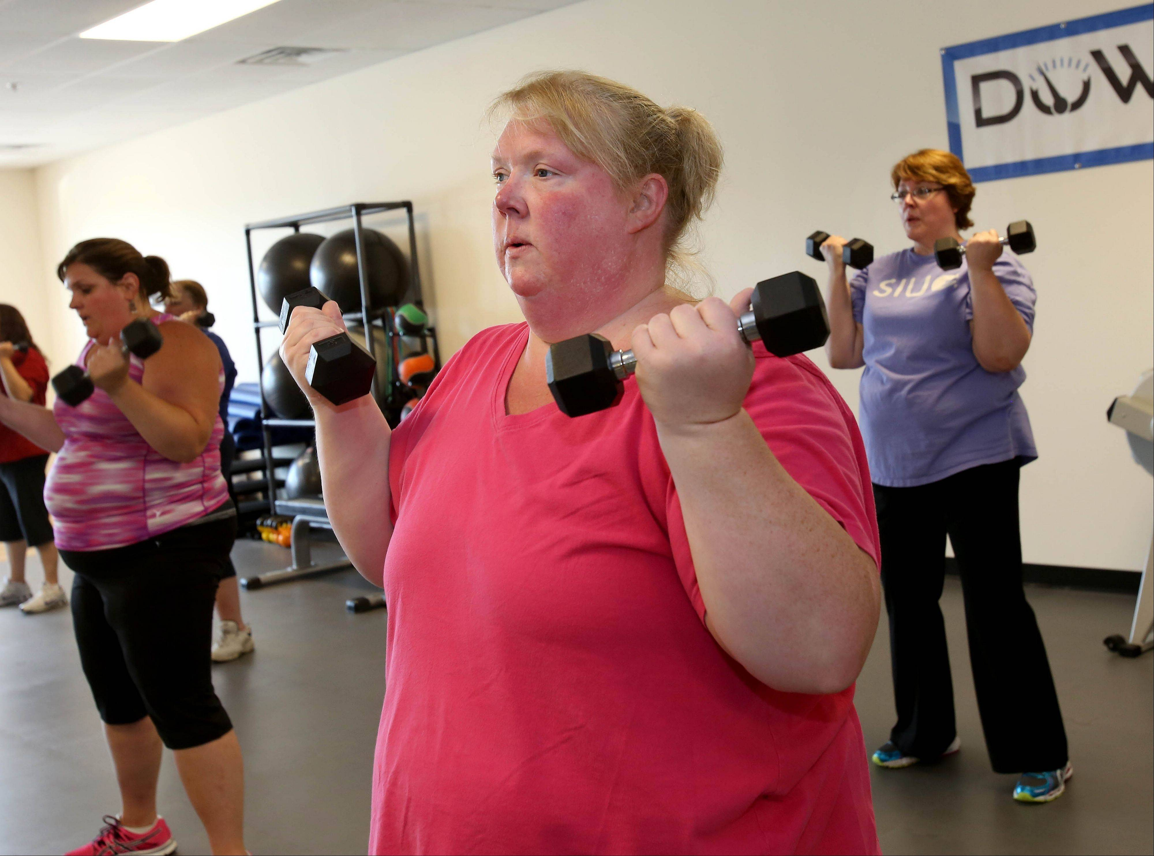 Kim Tremblay of Bolingbrook does curl presses during a recent workout at Downsize Fitness in Naperville. The gym offers semiprivate classes tailored to people who have at least 50 pounds to lose.