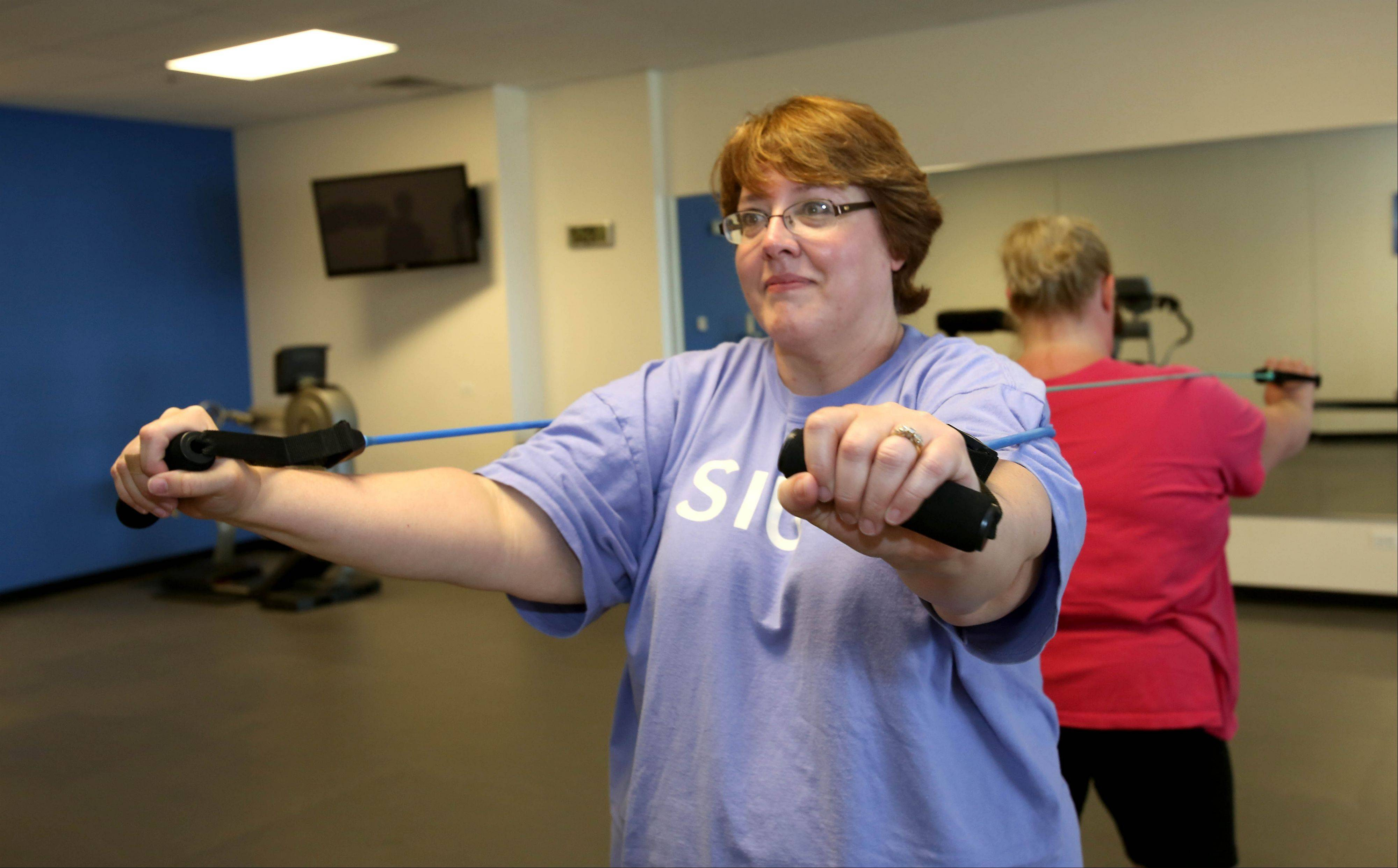 Diane Reiter of Aurora uses a resistance band during a recent workout at Downsize Fitness in Naperville. Downsize has locations in Chicago, Dallas, New York City and Naperville.
