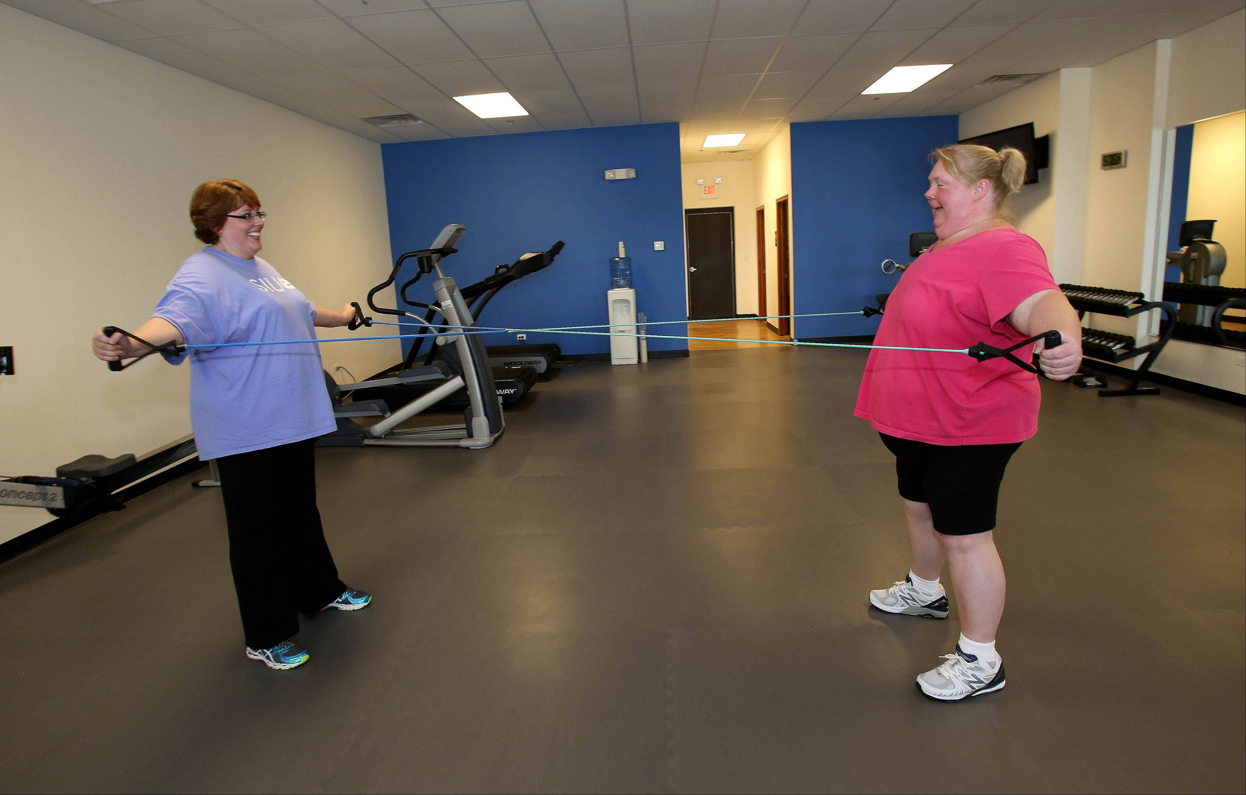 Diane Reiter of Aurora partners with Kim Tremblay of Bolingbrook for circuit training with resistance bands during a recent workout at Downsize Fitness, a new gym in Naperville for people who have at least 50 pounds to lose.