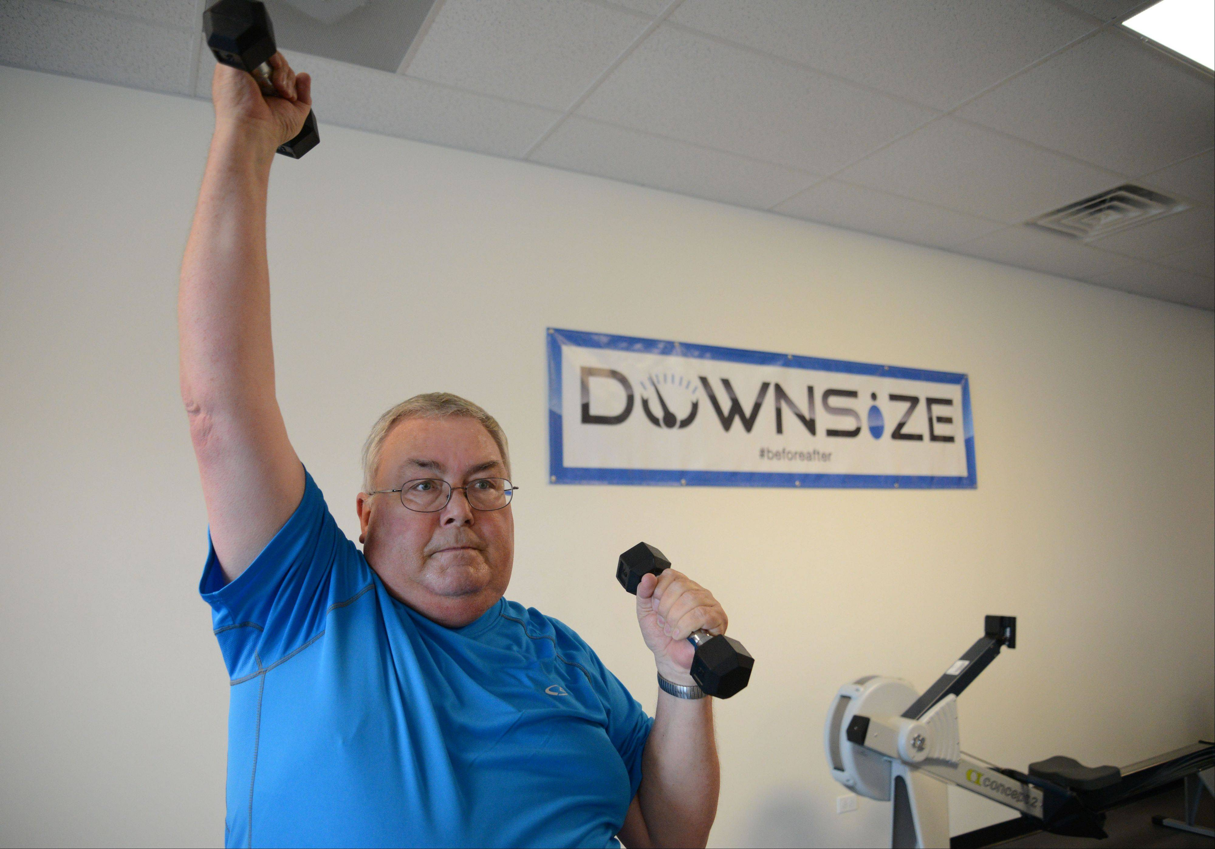 "Kent Huffman of Naperville works out with free weights Wednesday in Naperville at the first suburban location of Downsize Fitness, which bills itself as ""the world's first overweight-only gym."""
