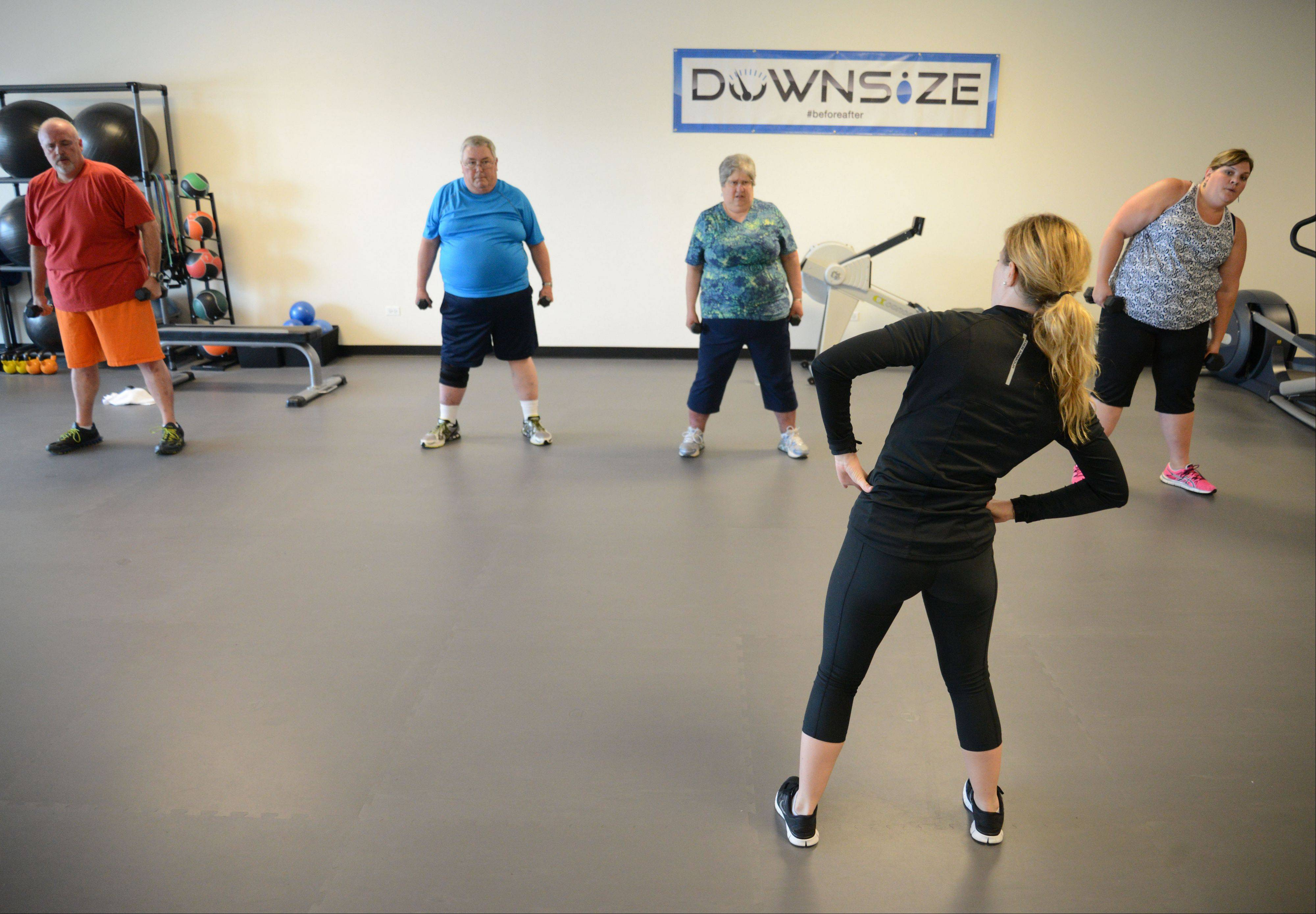 Jillian McAfee, general manager of Downsize Fitness in Naperville, leads a small group at the new gym for people who have at least 50 pounds to lose.