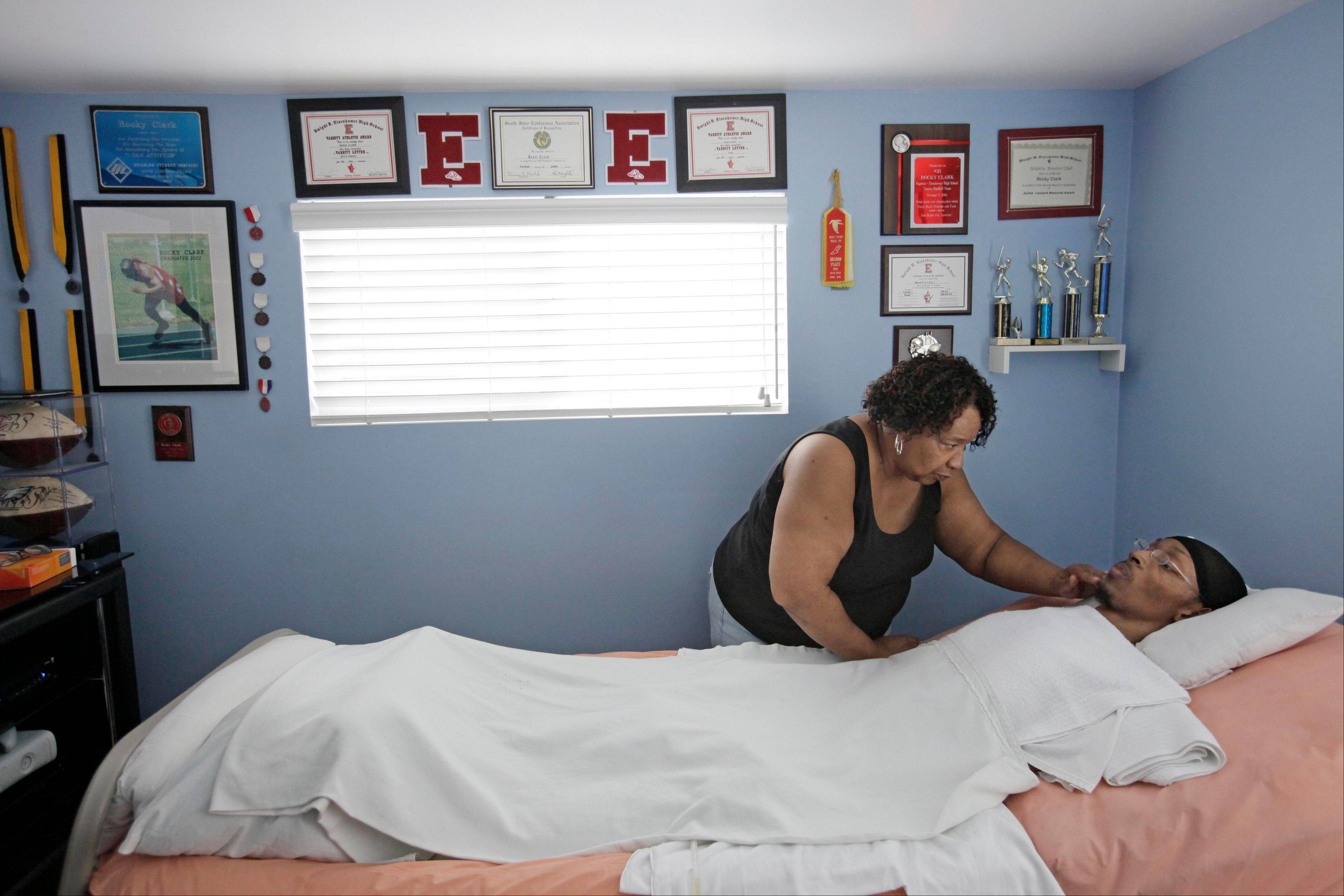 "Rocky Clark, a former Illinois high school football player who became a quadriplegic after his neck was broken while being tackled during a play in 2000, is cared for my his mother Annette Clark in his home, in Robbins. Clark who played football for Eisenhower High School in Blue Island, was remembered Sunday at the school as Illinois Gov. Pat Quinn signed legislation which will be known as ""Rocky's Law"". The law requires public and private school districts to provide catastrophic accident insurance for students who are injured while participating high school-sponsored or supervised athletic events."