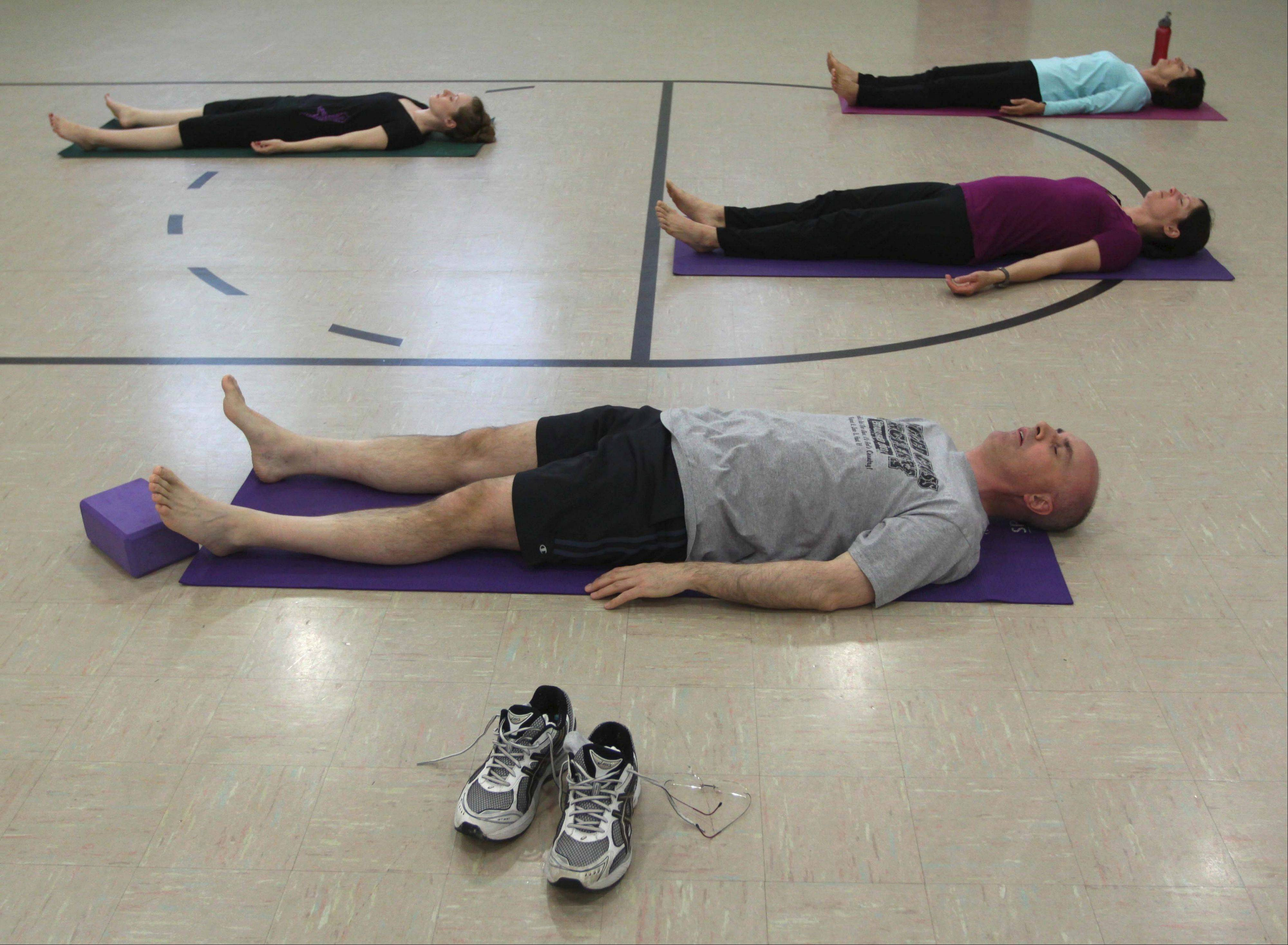 Erin Marth, left, Marty Anderson, Deb McMahon and Judy Besch meditate during a Holy Yoga class.