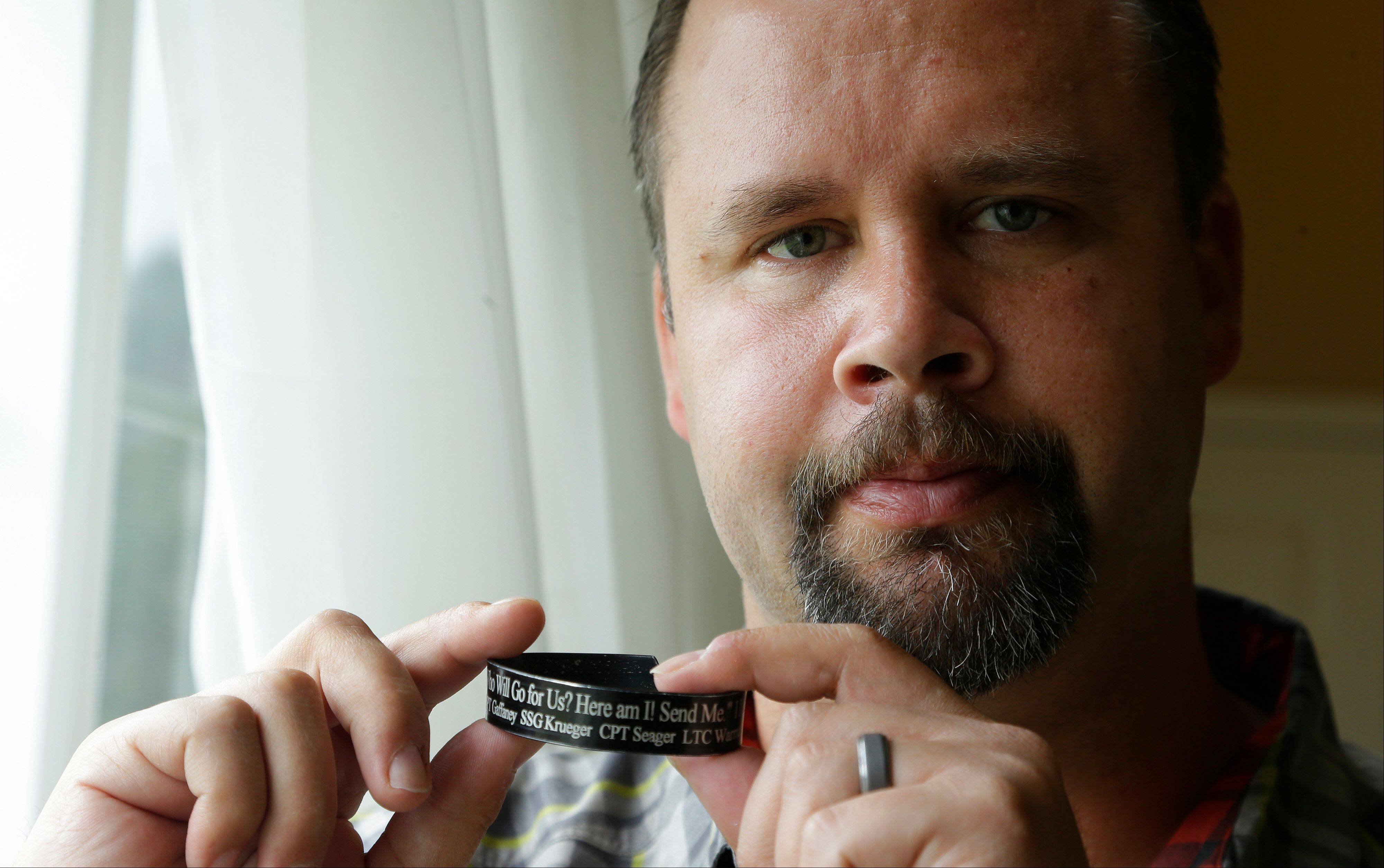 In this Saturday, Aug. 3, 2013, photo, retired U.S. Army Staff Sgt. Shawn Manning poses for a photo, at his home in Lacey, Wash., as he holds a memorial bracelet for members of his military unit who were killed in a 2009 mass shooting at Fort Hood, Texas. Manning, who still carries two bullets in his body from the shooting that killed 13 people, is scheduled to testify at the court martial for Maj. Nidal Malik Hasan, the accused shooter this week.