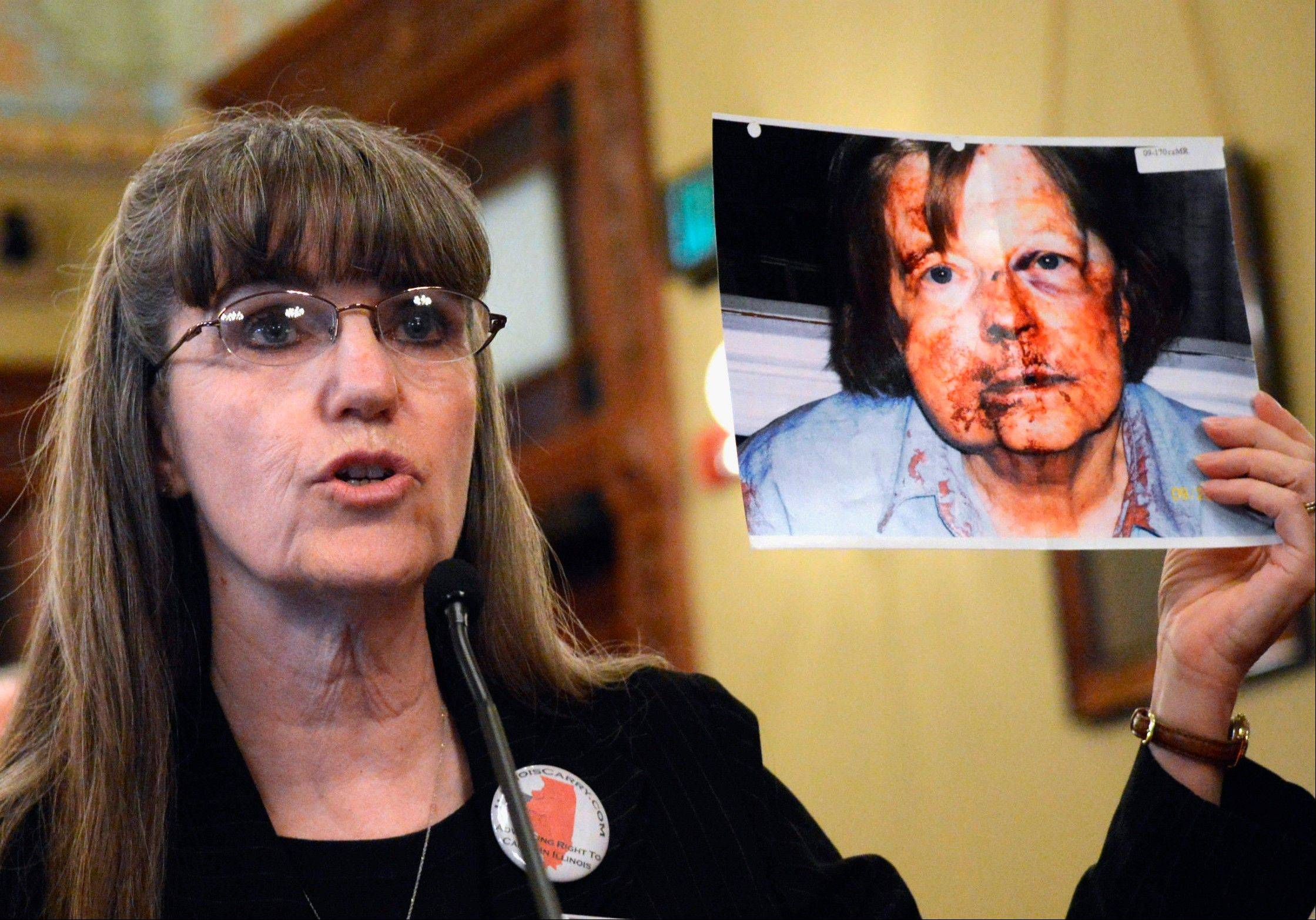 Valinda Rowe, spokeswoman for Illinois Carry, holds a photograph of Mary Shepard, a downstate woman who was beaten in 2009 by an intruder at her workplace. Shepard has said that had she not been barred from carrying a gun, she could have thwarted the attack.