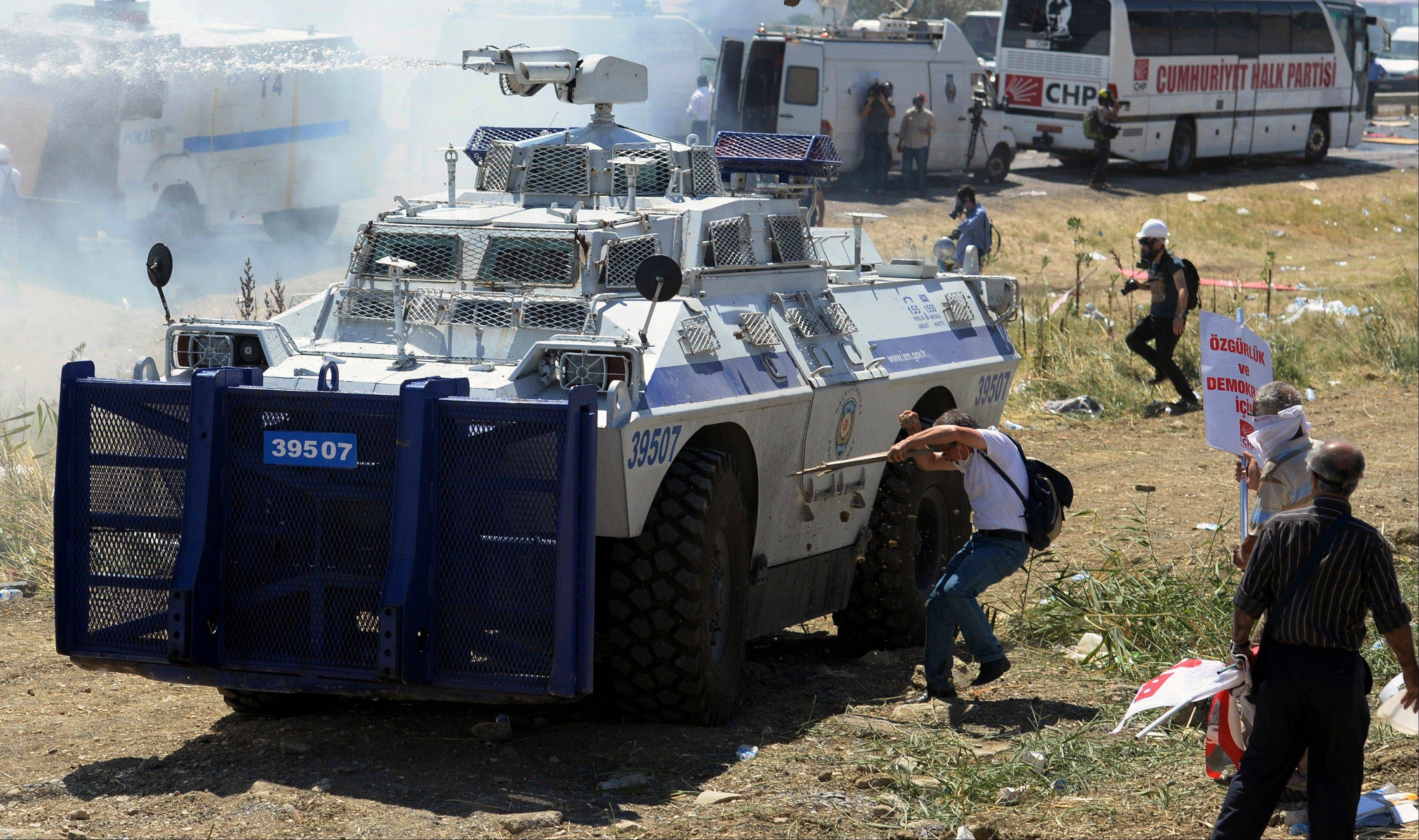 Protesters clash with riot and paramilitary polices as they fire tear gas and use water cannons to disperse them outside the Silivri jail complex in Silivri, Turkey, Monday, Aug. 5, 2013. Some 275 people � including military officers, politicians and journalists � are facing verdicts in a landmark and divisive trial in Turkey over an alleged conspiracy to overthrow the government. The court has acquitted 21 people accused of plotting to overthrow the Islamist-rooted government in the five-year �Ergenekon� trial and sentenced of up to 47 years or life terms in jails some of the other 254 defendants.