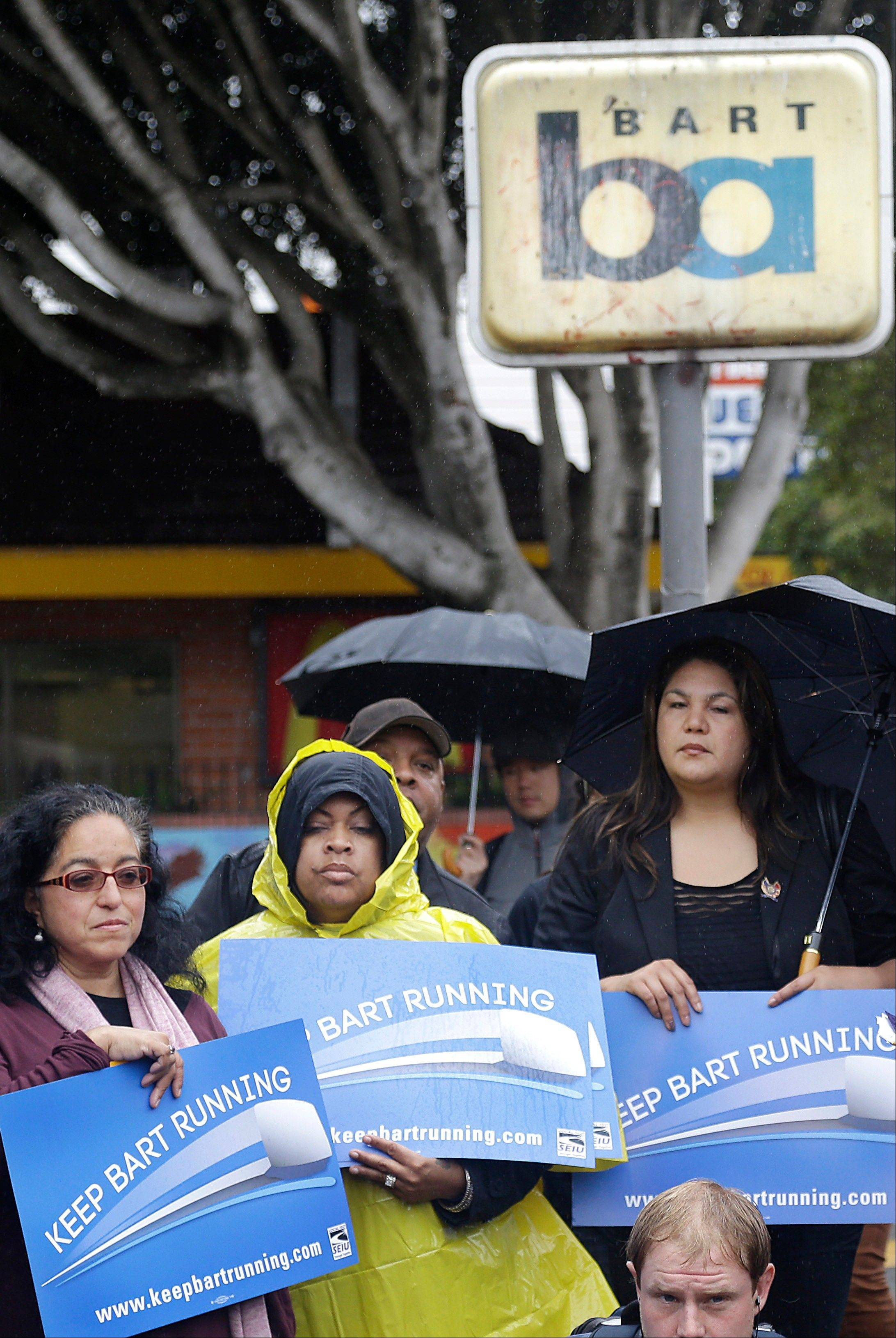 In this file photo from Tuesday, June 25, 2013, supporters of Bay Area Rapid Transit workers hold up signs at a news conference outside of the BART 24th Street Mission station in San Francisco. Hundreds of thousands of San Francisco Bay Area commuters got at least a temporary reprieve from a massive transit strike when Gov. Jerry Brown ordered an inquiry into a labor contract dispute.