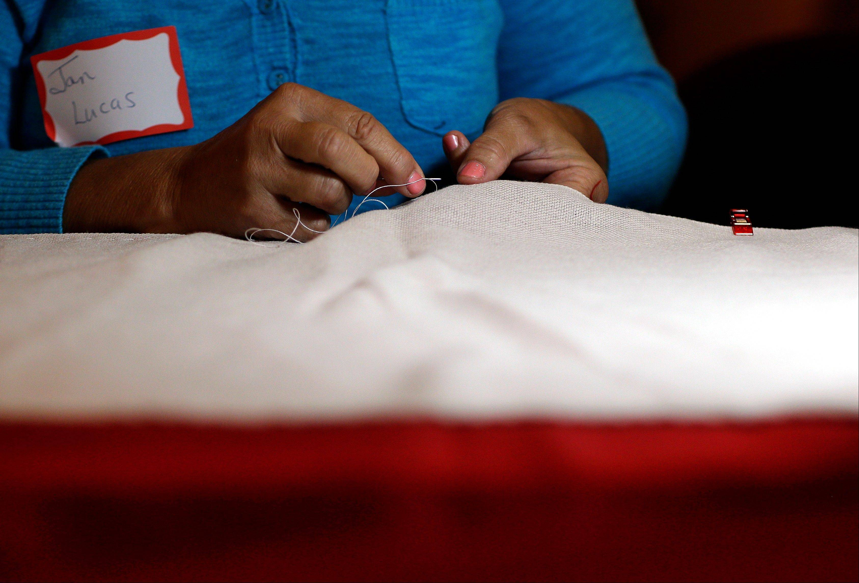 Volunteer Jan Lucas sews part of a replica of the star-spangled banner in Baltimore as part of a project to commemorate the creation of the flag that inspired Americaís national anthem.