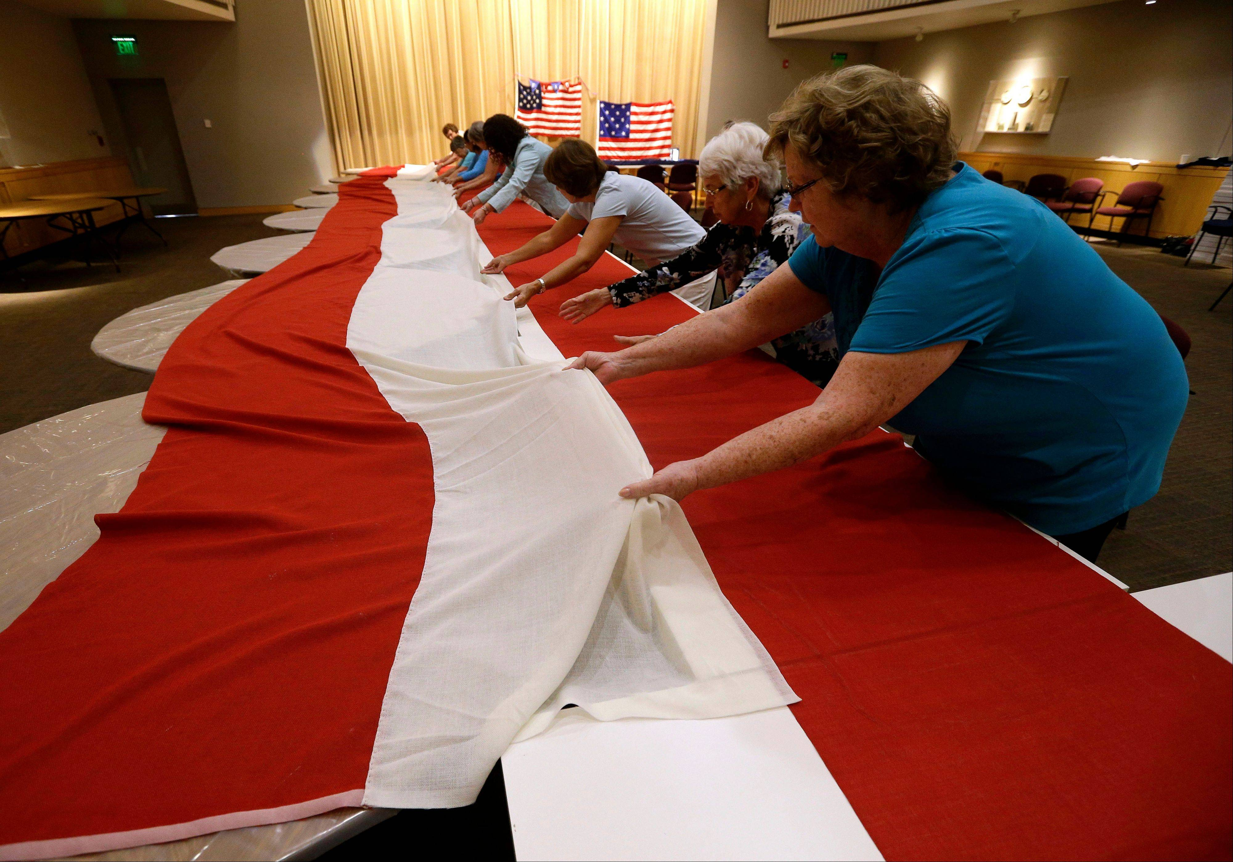 Volunteers line up stripes that, when hand-stitched together, will be part of a replica of the star-spangled banner.