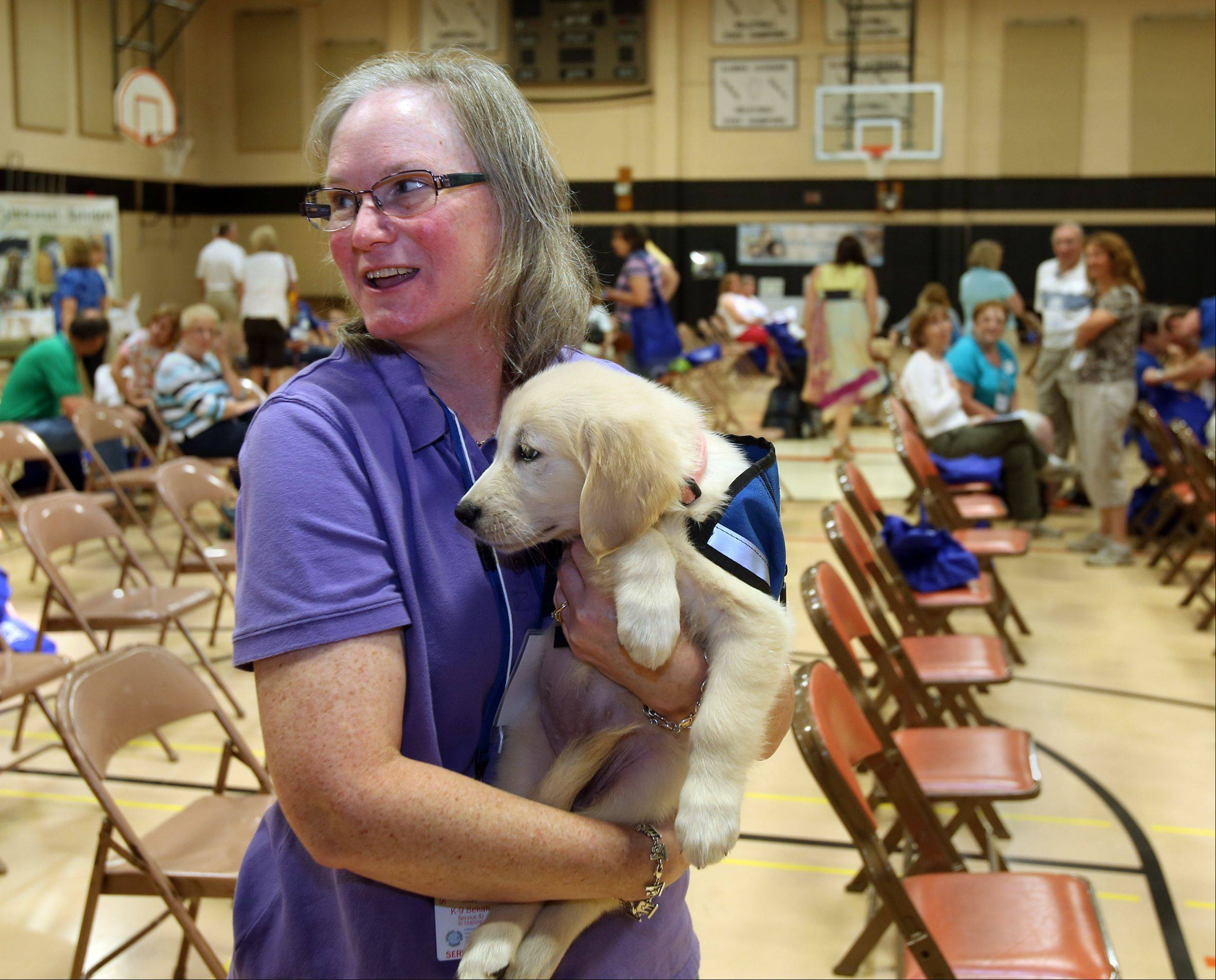 Mary Trapp of Villa Park holds 10-week-old comfort dog Shiloh during the meeting for the K-9 Comfort Dog Ministry held this year at the Trinity Lutheran Church in Roselle.