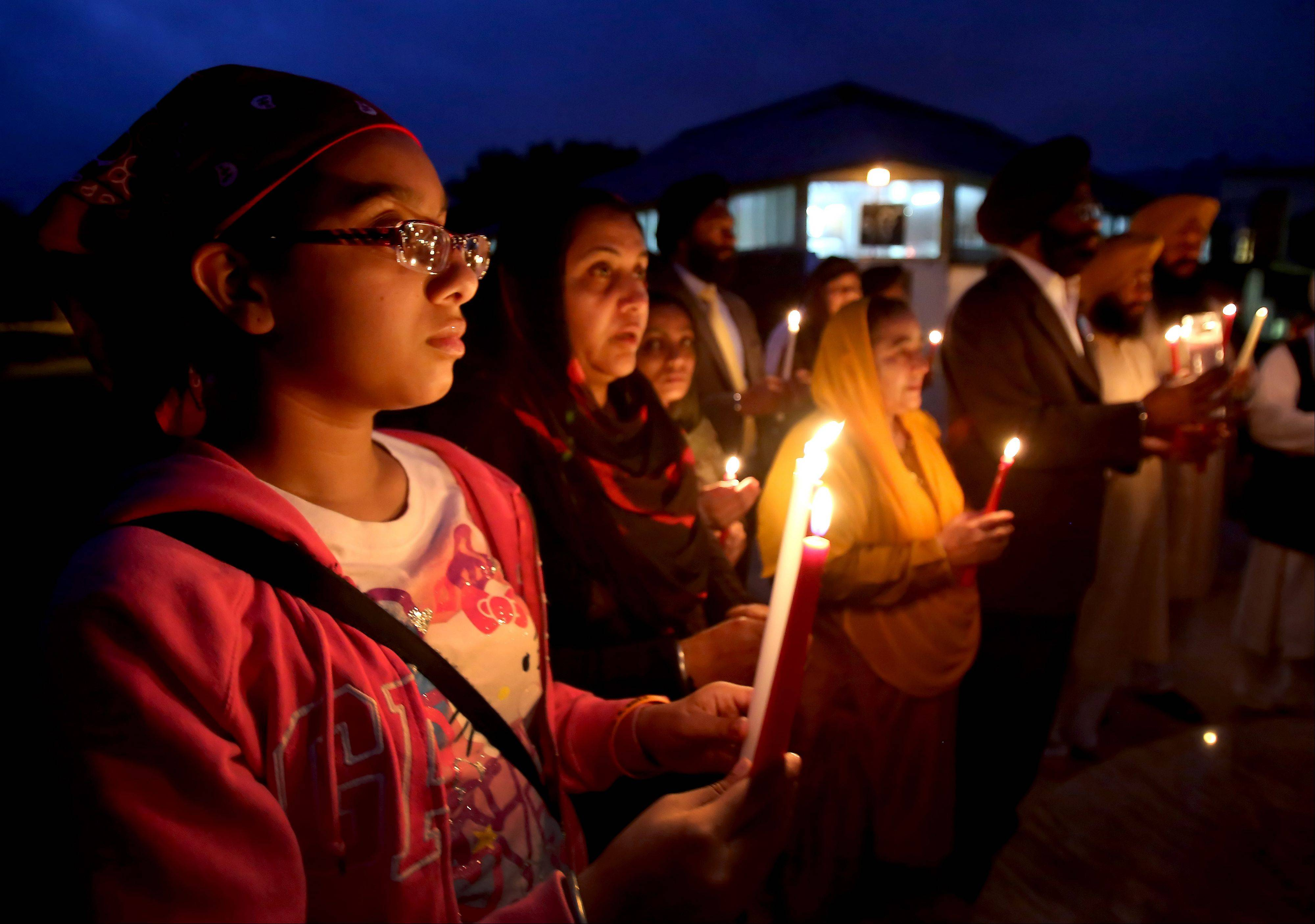 Baninder Clair, 14, left, and her mother, Jutinder Kaur, of Glendale Heights, right, participate in the vigil Monday at the Sikh gurdwara in Palatine.