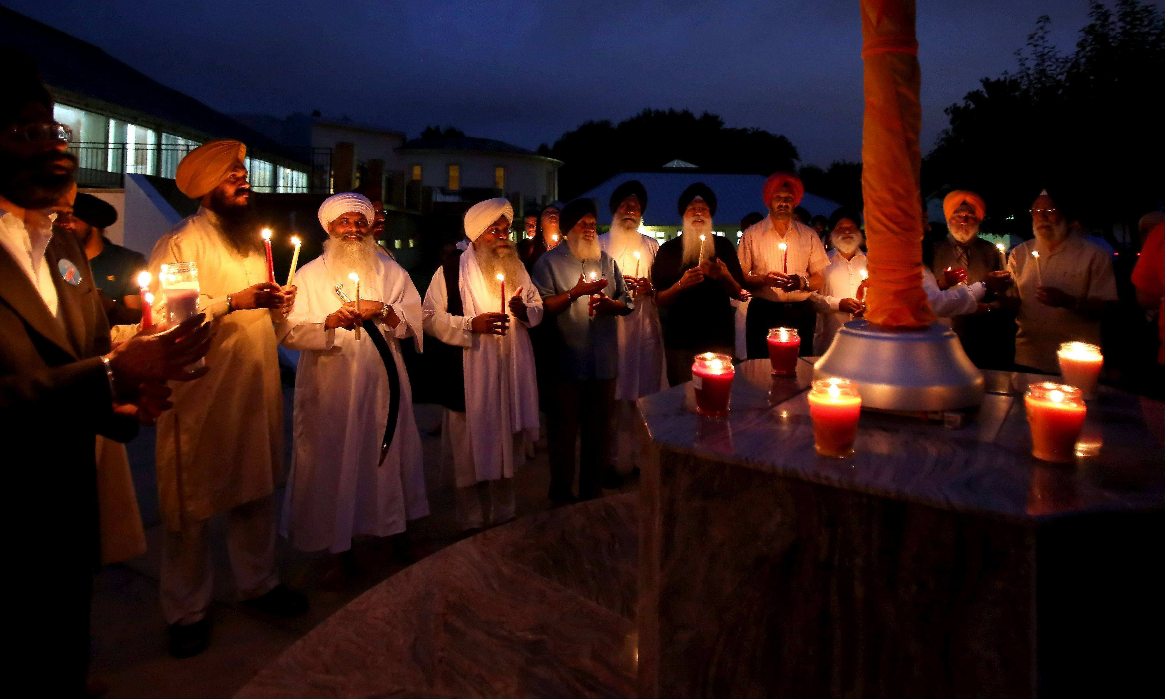 Members of the gurdwara in Palatine hold a vigil Monday to commemorate victims of the shooting at a Sikh temple near Milwaukee one year ago.