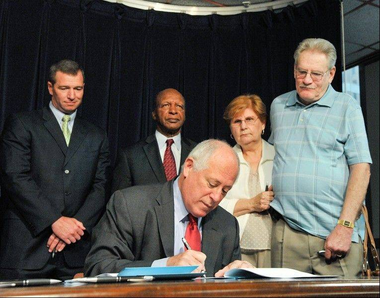 "Gov. Patrick Quinn signs ""Patricia's Law"" Monday as the parents of Patricia McNamara, Carol and Wally Spears, right, watch. The law prevents people charged as the result of a fatal accident from receiving court supervision if they've had court supervision in the past."
